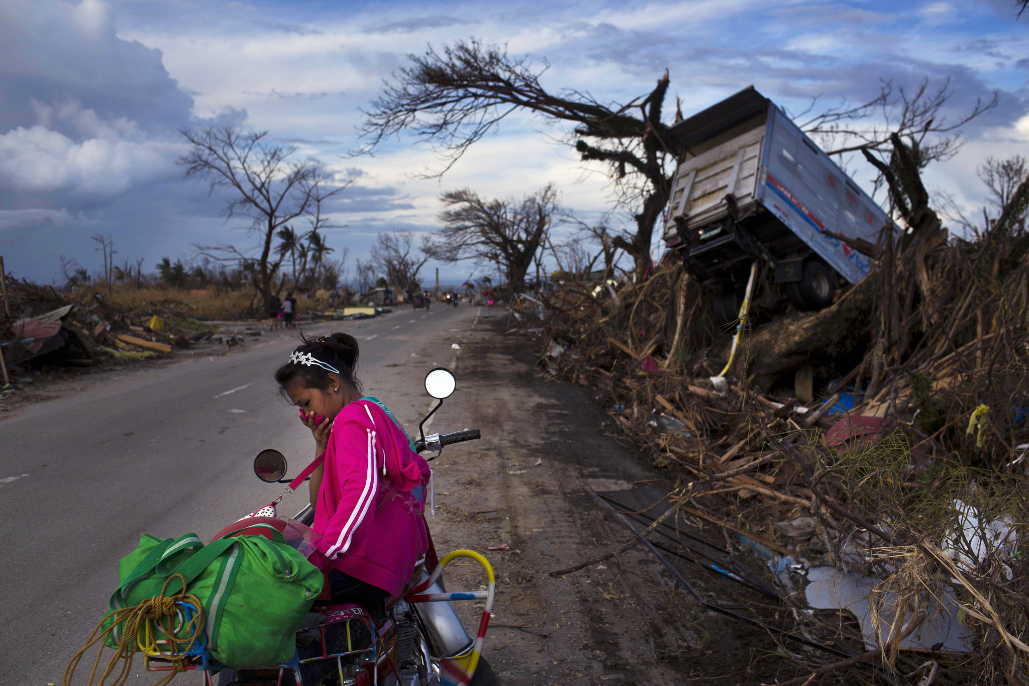 A woman rests on a roadside with her family's belongings near the Typhoon Haiyan ravaged town of Tacloban, central Philippines on Wednesday, Nov. 13, 2013. Typhoon Haiyan, one of the most powerful storms on record, hit the country's eastern seaboard on Friday, destroying tens of thousands of buildings and displacing hundreds of thousands of people.
