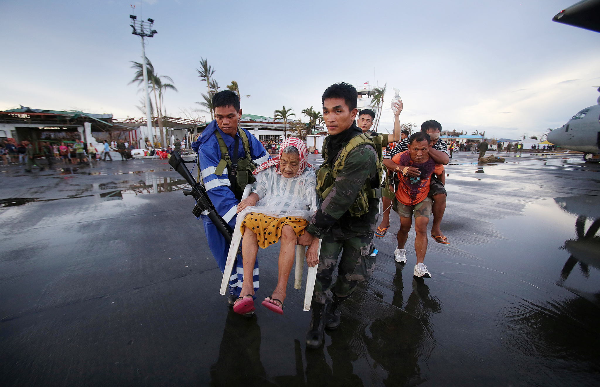 Survivors of Typhoon Haiyan are evacuated by rescue workers from the airport in Tacloban city, Leyte province, central Philippines, Tuesday, Nov. 12, 2013. Four days after Typhoon Haiyan struck the eastern Philippines, assistance is only just beginning to arrive.