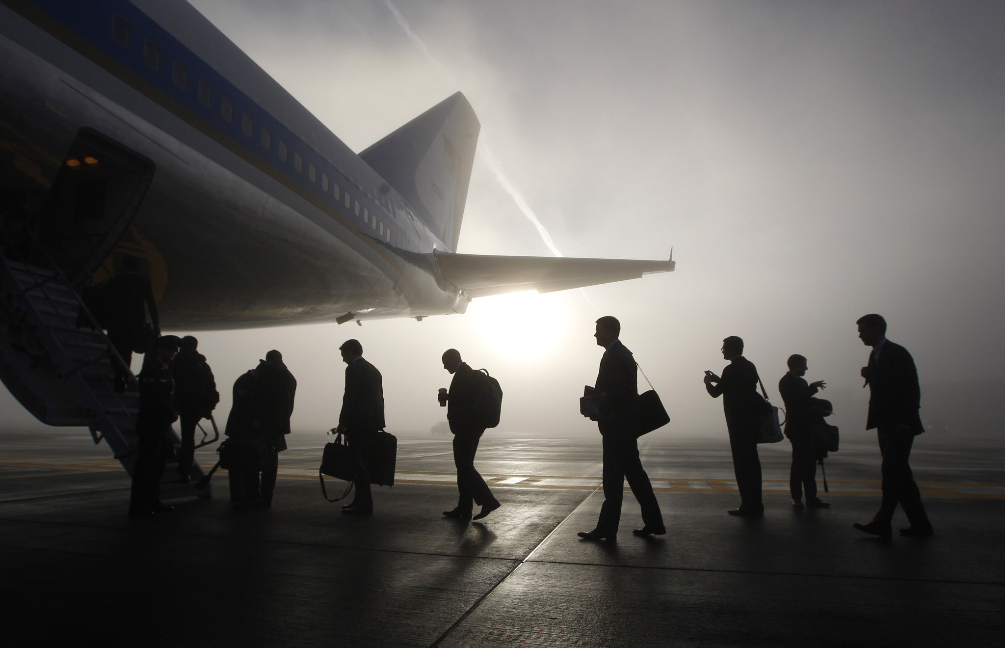 Travelling White House staff and press board the rear steps of Air Force One on a foggy morning in Seattle...Travelling White House staff and press board the rear steps of Air Force One on a foggy morning in Seattle, November 25, 2013. U.S. President Barack Obama is attending fundraisers and events on the economy and immigration in Los Angeles and San Francisco on Monday.