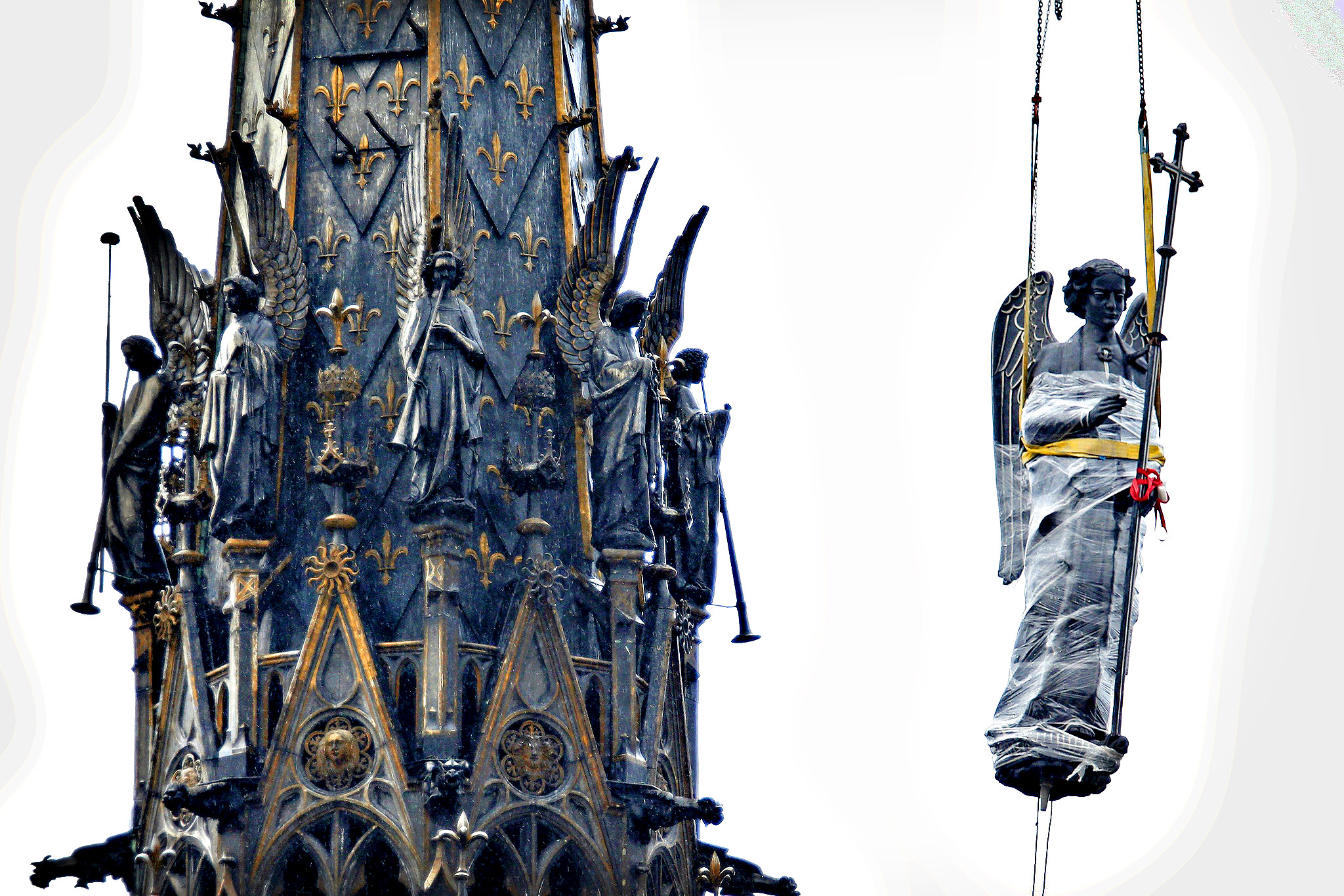 The restored statue archange Saint Michel (Saint Michael Archangel) is lifted up next to the spire of the Sainte-Chapelle (Holy Chapel) in Paris November 14, 2013. The reinstallation of the statue is part of the restoration of  the Chapel, located within the Palais de Justice complex on the Ile de la Cite in Paris, which has started in 2008 and will finish at the end of 2014.