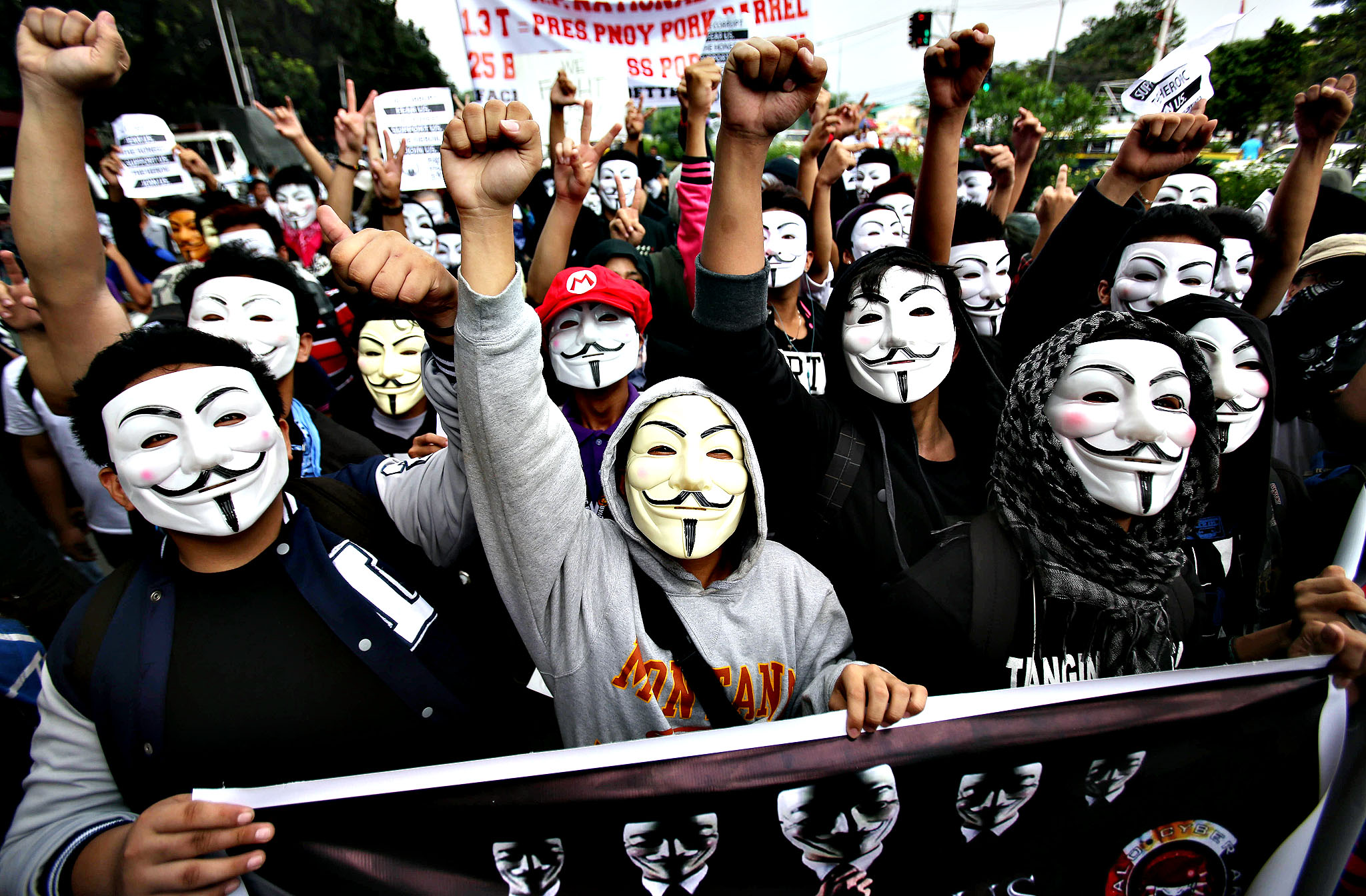 "student protesters wearing masks raise their clenched fist as they pass by the gates of the House of Representatives in suburban Quezon city, north of Manila, Philippines on Tuesday Nov. 5, 2013. Supporters of hacker group Anonymous Philippines held the rally to call for the abolition of all forms of ""pork barrel"" funds after allegations that several members of the House of Representatives and the Philippine Senate conspired with wealthy businesswoman Janet Lim Napoles to steal huge amounts of government development funds. Napoles is set to appear before the Senate Blue Ribbon Committee on Nov. 7."