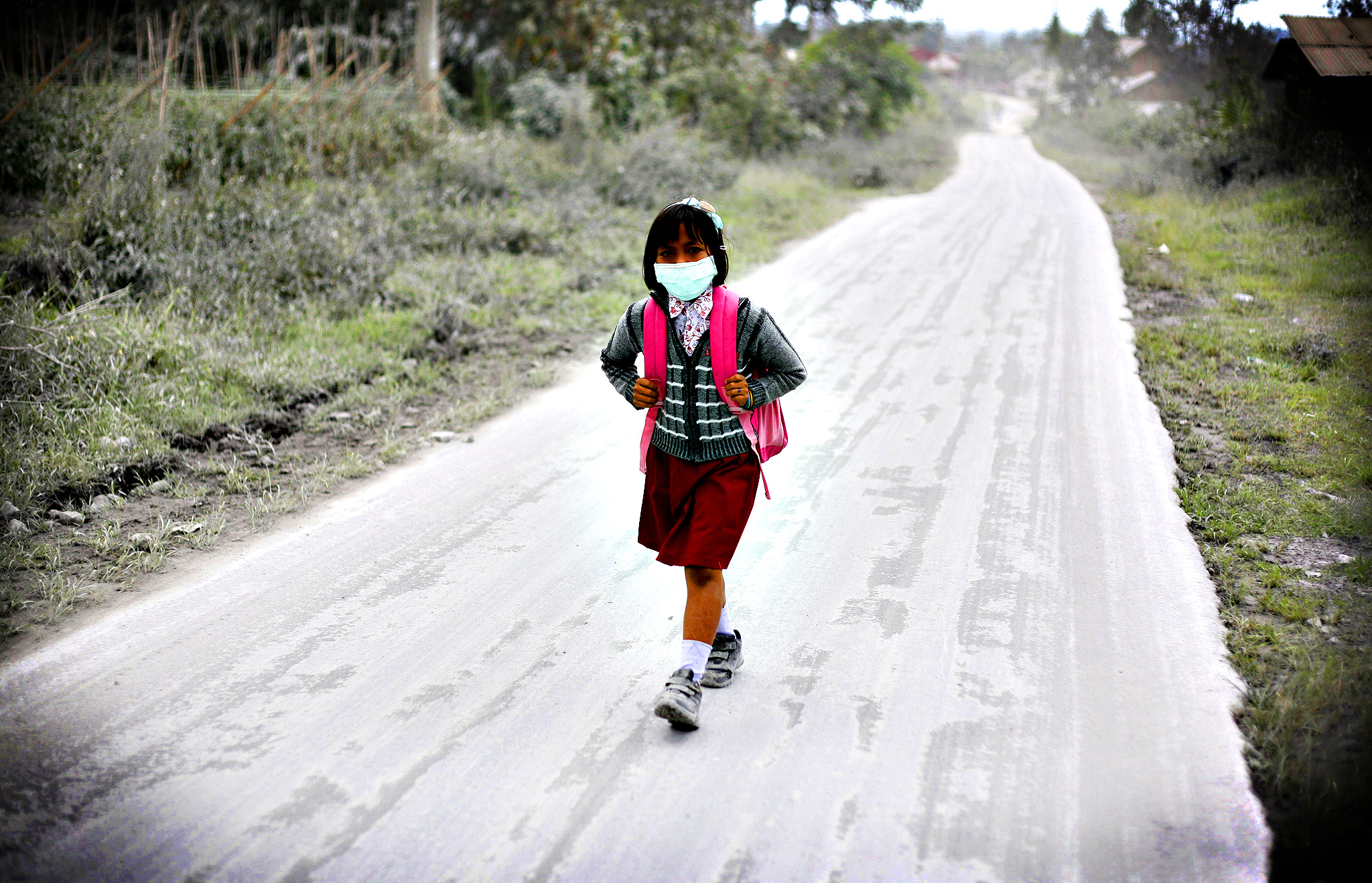 A student walks on a road covered with volcanic ash from the eruption of Mount Sinabung in Tiga Nderket, North Sumatra, Indonesia, Wednesday, Nov. 6, 2013. The 2,600-meter (8,530-foot) -high volcano has been erupting since Sunday, unleashing volcanic ash high into the sky and forcing the evacuation of villagers living around its slope.