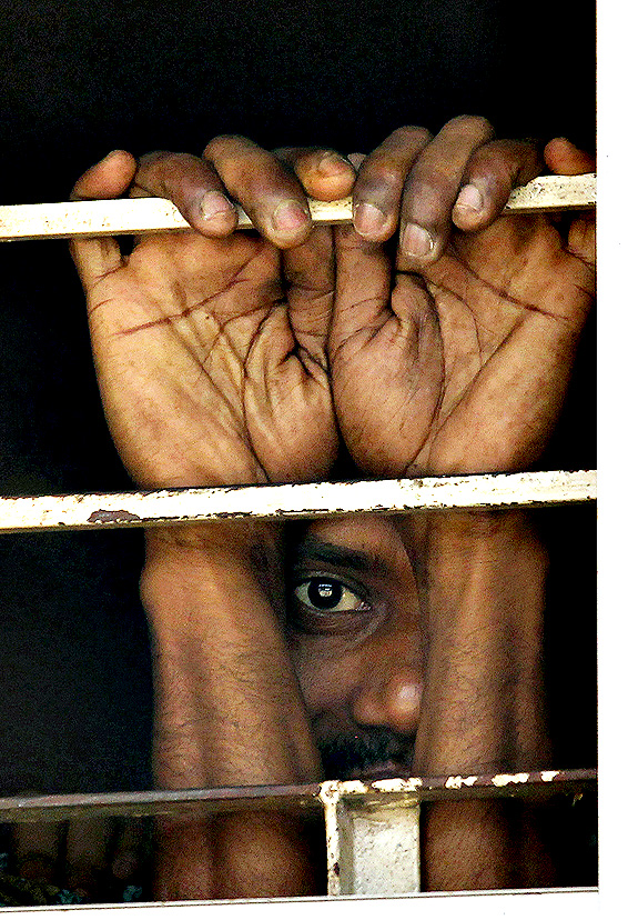 A prisoner stands looking out of a window of a courthouse before the verdict for a 2009 mutiny is announced, in Dhaka November 5, 2013. A special court in Bangladesh on Tuesday sentenced to death more than 150 people, from among hundreds of mutineers accused of murder and arson at the headquarters of the country's border guards in 2009.