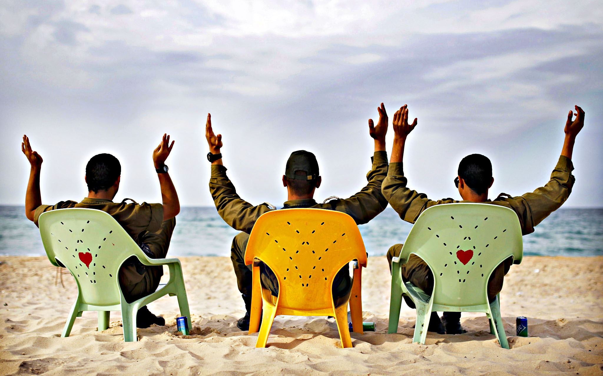 Israeli soldiers gesture as they sit in front of the Mediterranean at Zikim beach, near the southern city of Ashkelon November 27, 2013. Unseasonable temperatures reaching 32 degrees Celsius were recorded in some areas of Israel on Wednesday.