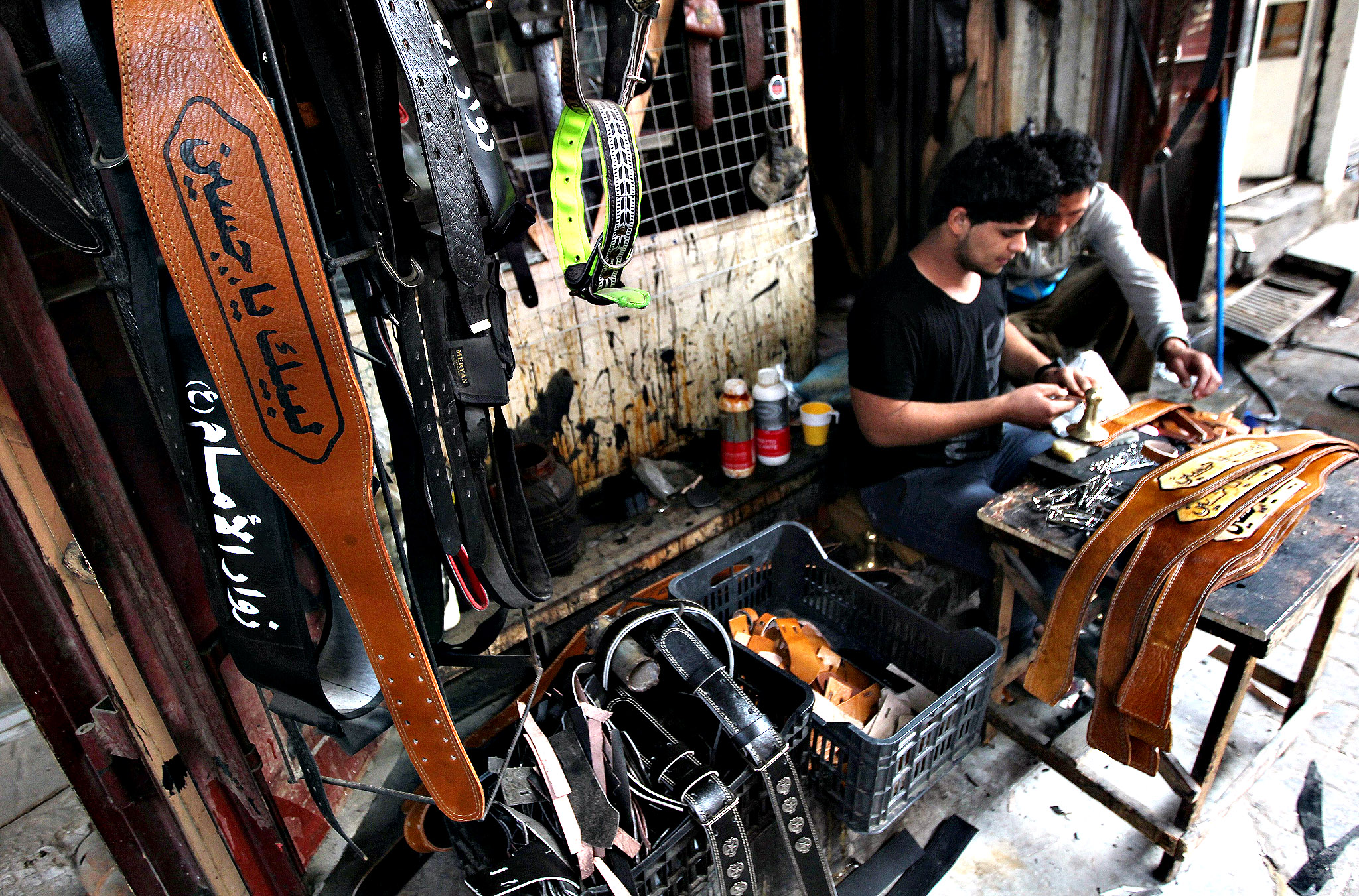"An Iraqi youth makes a belt especially for the annual Shiite Muslim commemoration of Ashura with the saying embossed in Arabic that reads, ""Labaik ya Hussein"" or "" In your service Hussein"", referring to the grandson of the Prophet Mohammed, at a work shop in Baghdad on November 4, 2013."