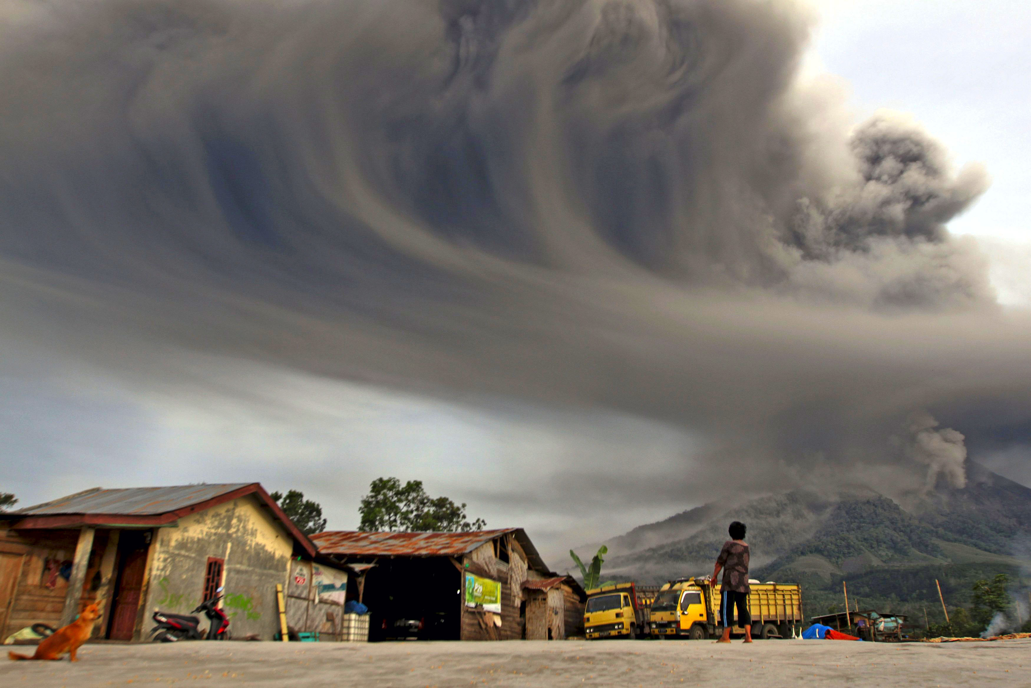 A woman looks on as Mount Sinabung spews ash, as pictured from Sibintun village in Karo district