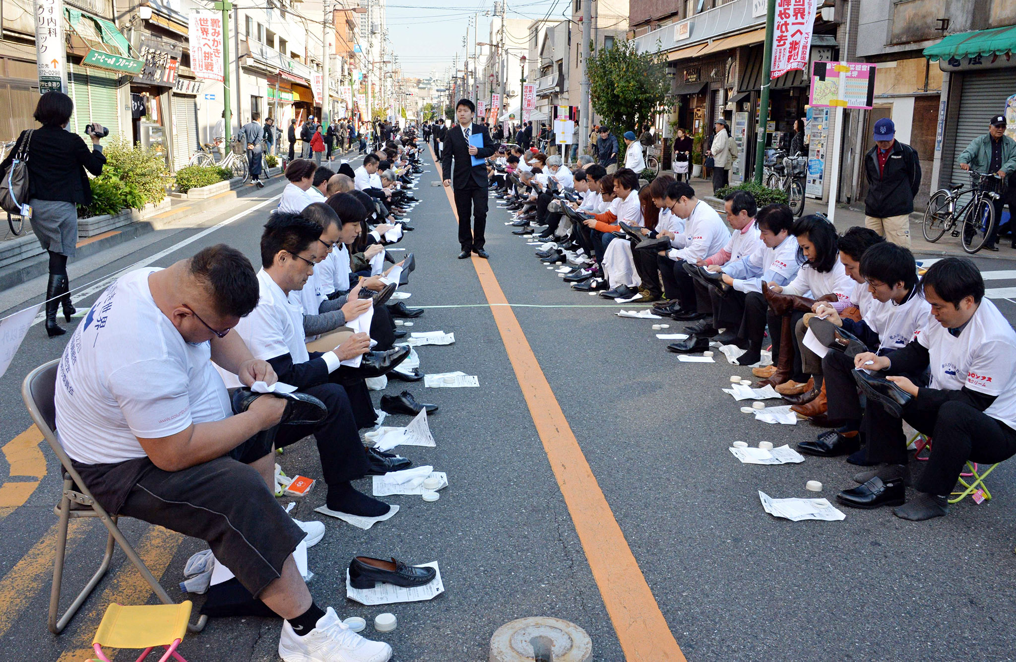 "Some 800 participants polish their leather shoes on a street in Tokyo's Taito ward, a district famous for its shoemakers in Japan, to challenge the record of ""most people polishing shoes"" for the Guinness Book of World Records on November 22, 2013. Participants established a new world record over the previous one, made with 451 people in the UAE in 2011.       AFP PHOTO / Yoshikazu TSUNOYOSHIKAZU TSUNO/AFP/Getty Images"