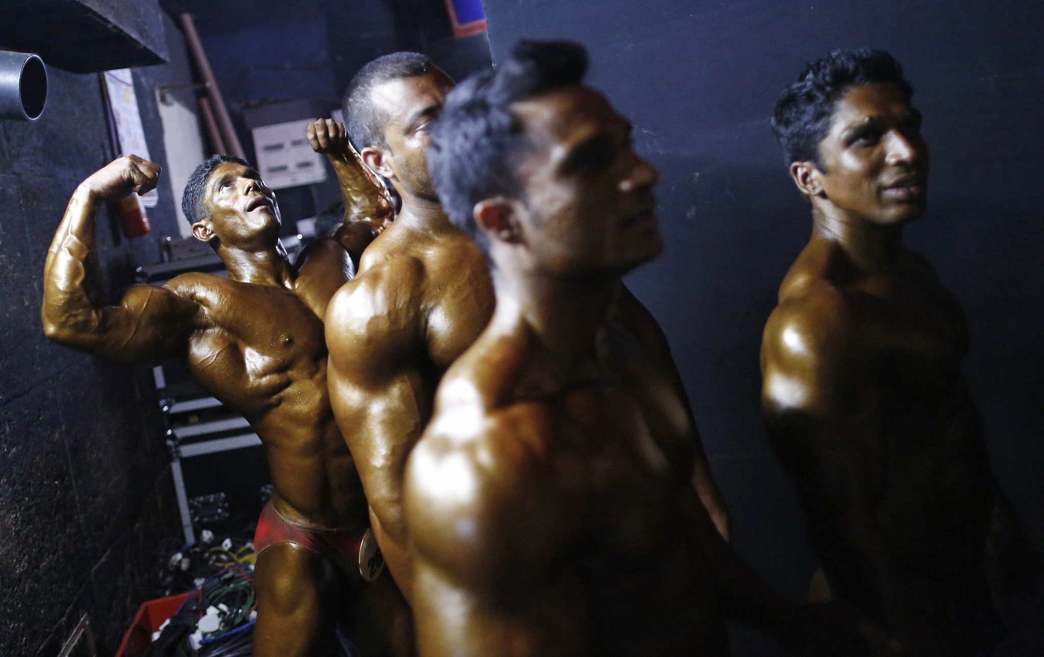 Competitors wait to get on the stage during a bodybuilding competition in Mumbai...Competitors wait to get on the stage during a bodybuilding competition in Mumbai November 27, 2013. Around 30 bodybuilders from all parts of India participated in the competition.