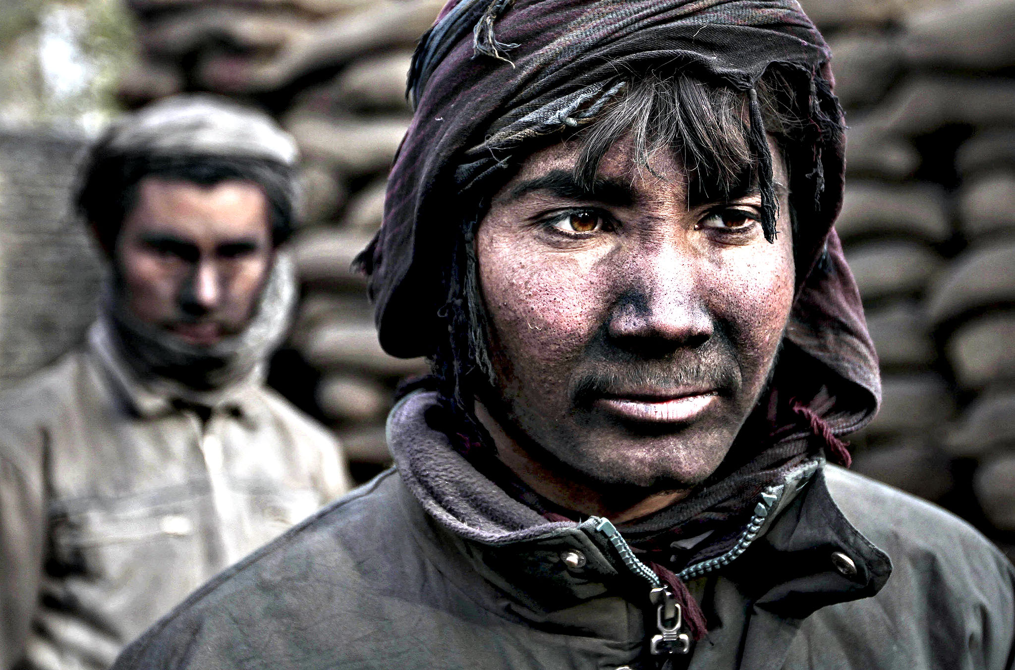 Qudrat, 18, right, poses for a photograph as he works at a charcoal shop on the outskirts of Kabul, Afghanistan, Monday, Nov. 4, 2013. As winter is approaching, wood and charcoal are getting expensive among all other necessities for most Afghans.