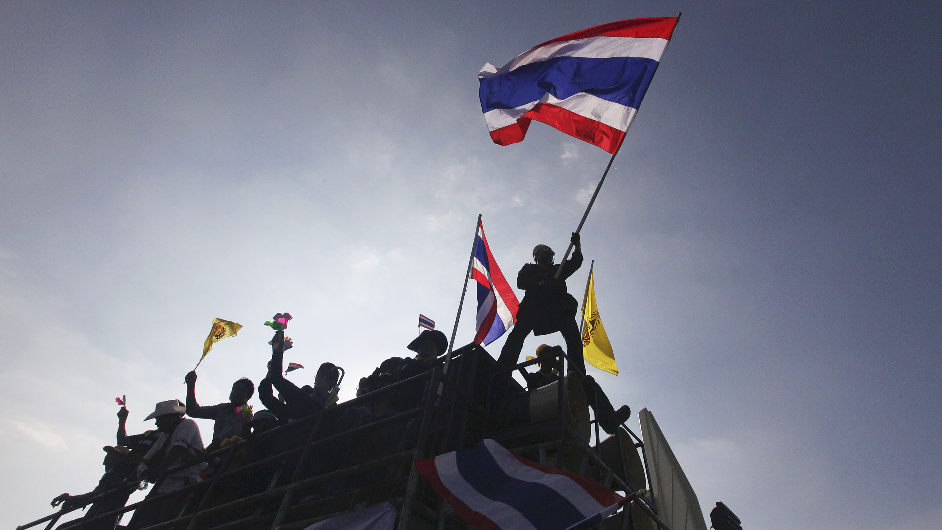 A protester waves a Thai national flag atop a truck at the Democracy Monument in central Bang