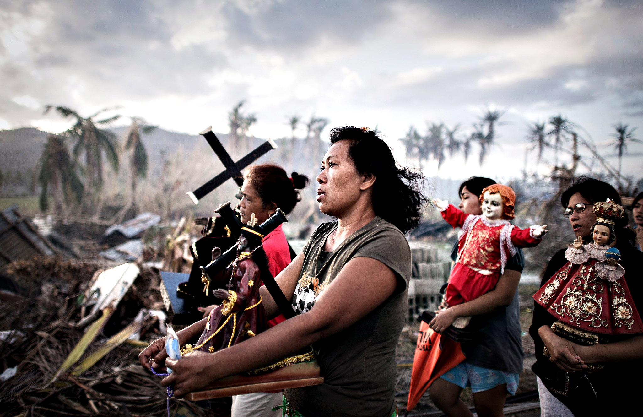 Survivors of Super Typhoon Haiyan march during a religious procession in Tolosa on the eastern Philippine island of Leyte on November 18, 2013 over one week after Super Typhoon Haiyan devastated the area.  The United Nations estimates that 13 million people were affected by Super Typhoon Haiyan with around 1.9 million losing their homes.