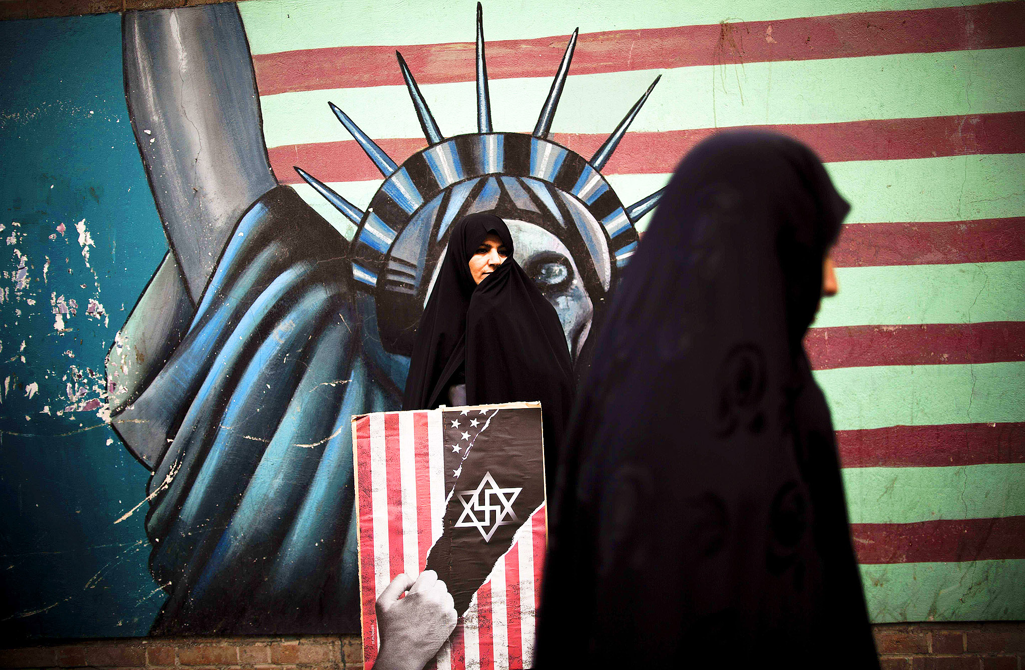 An Iranian woman holds an anti-US poster as she stands in front of a mural of the Statue of Liberty bearing the face of a skull on the wall of the former US embassy in Tehran on Monday, during a demonstration to mark the 34th anniversary of the 1979 US embassy takeover.