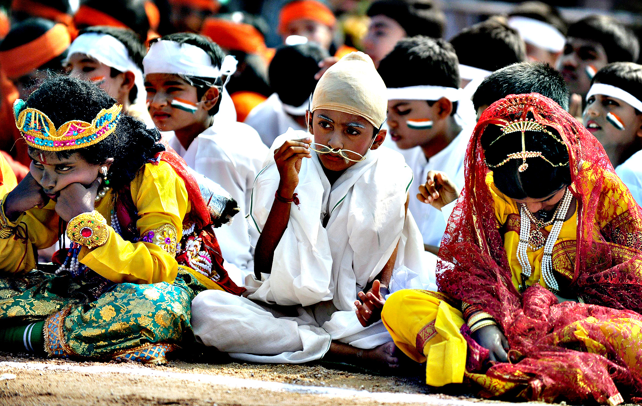An Indian school student dressed as Mahatma Gandhi (C) sits with fellow students as they take part in state formation day celebrations in Hyderabad