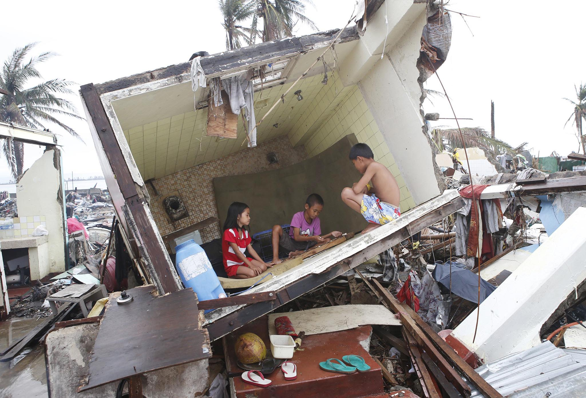 "Typhoon survivors play a game called ""Sungka"" inside the bathroom of a house in central Philippines"