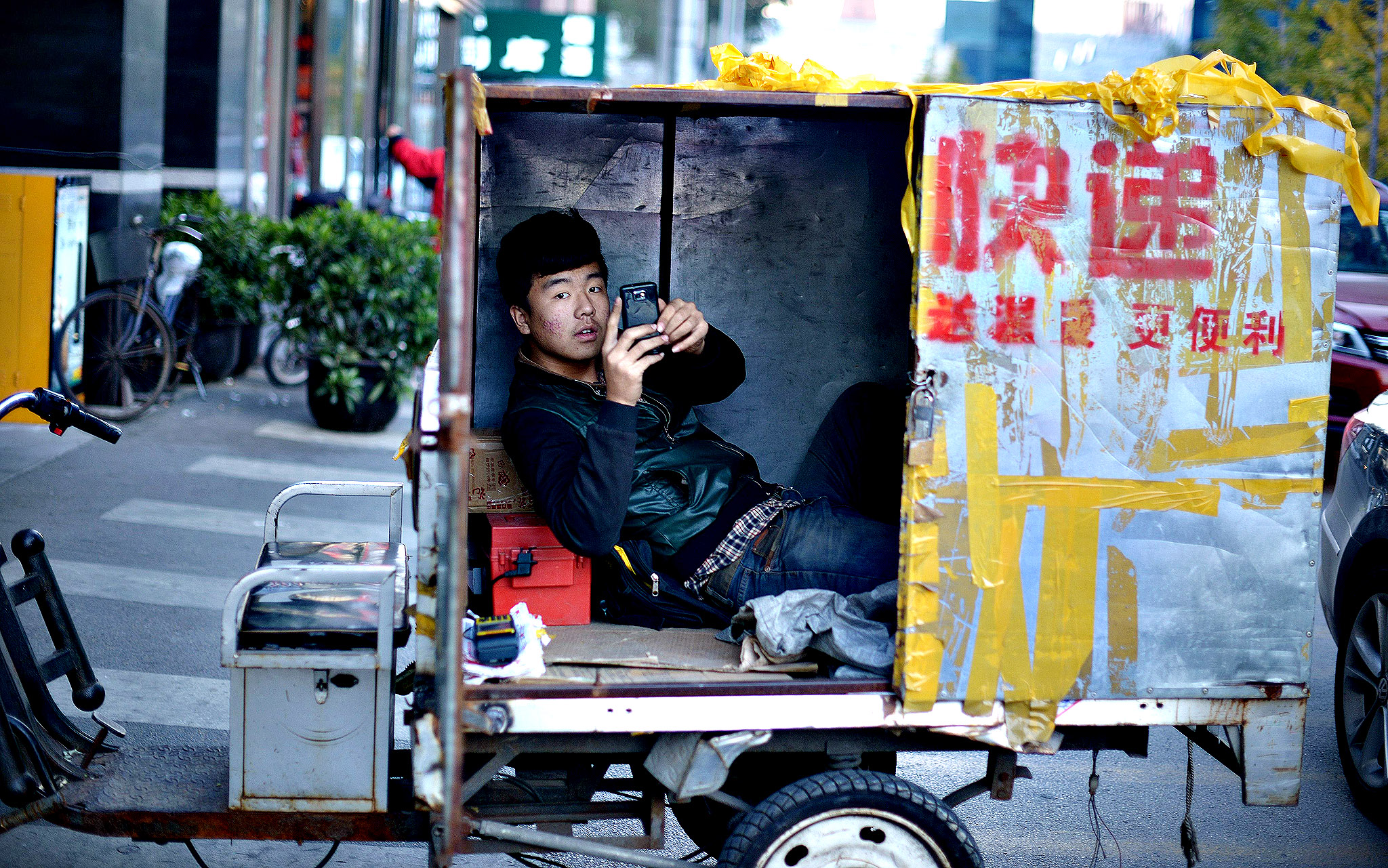 A delivery courier uses his mobile phone as he lies in a tricycle along a road  in Beijing on Monday. Chinese manufacturing grew at its strongest pace in 18 months in October.