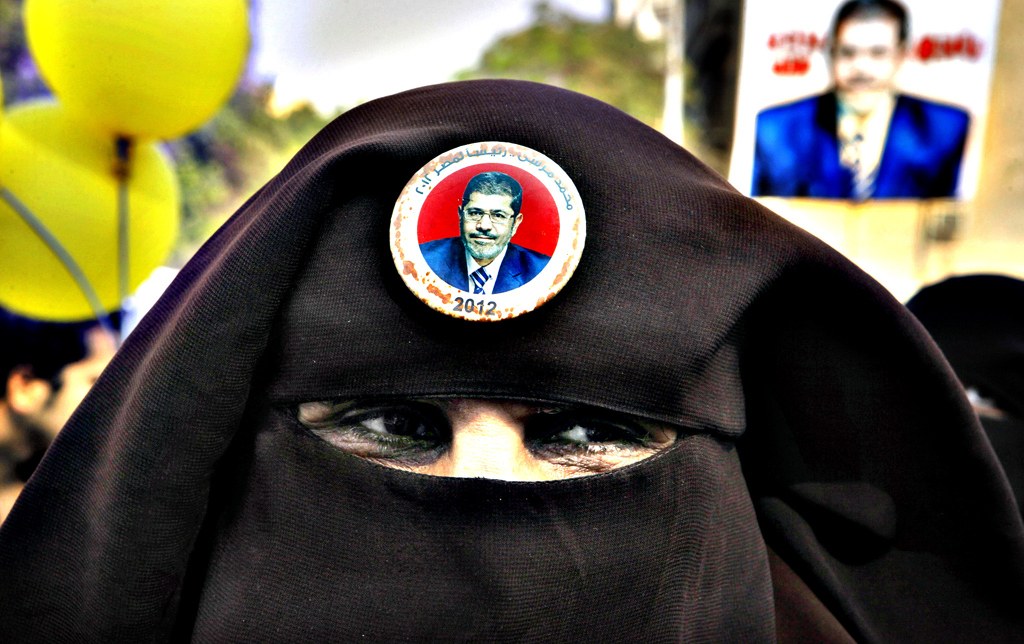 "A supporter of Egypt's ousted President Mohammed Morsi wears a button showing Morsi and a slogan in Arabic that reads, ""Morsi for Egyptian presidency 2012,"" during a protest in Cairo, Egypt, Friday, Nov. 1, 2013. Some 20,000 police officers and soldiers will guard the upcoming trial of Egypt's toppled president on Nov. 4, as Islamist opponents plan massive protests that may spark more turmoil in the country."