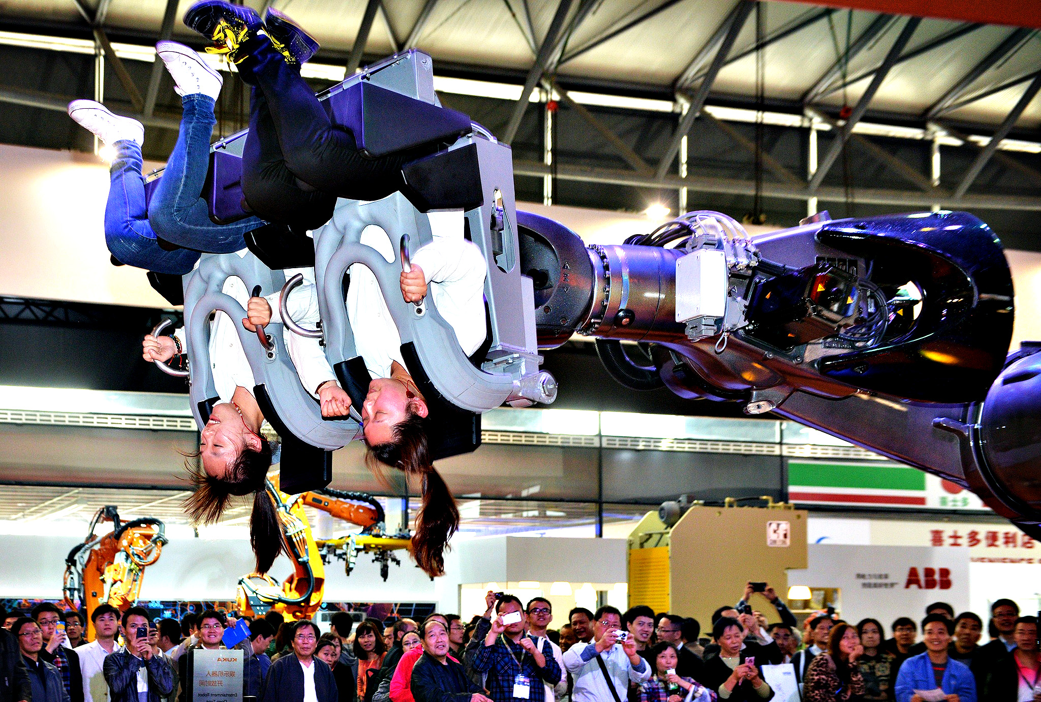 "Visitors ride in a robot arm called ""ROBOcoaster"" at the China International Industry Fair 2013 in Shanghai on November 6, 2013."