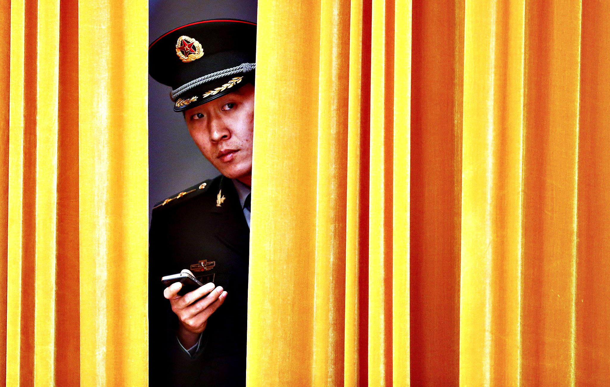 A member of the People's Liberation Army (PLA) is seen behind a curtain before a welcoming ceremony for Dutch Prime Minister Mark Rutte with his Chinese counterpart Li Keqiang (both not pictured) at the Great Hall of the People in Beijing, China