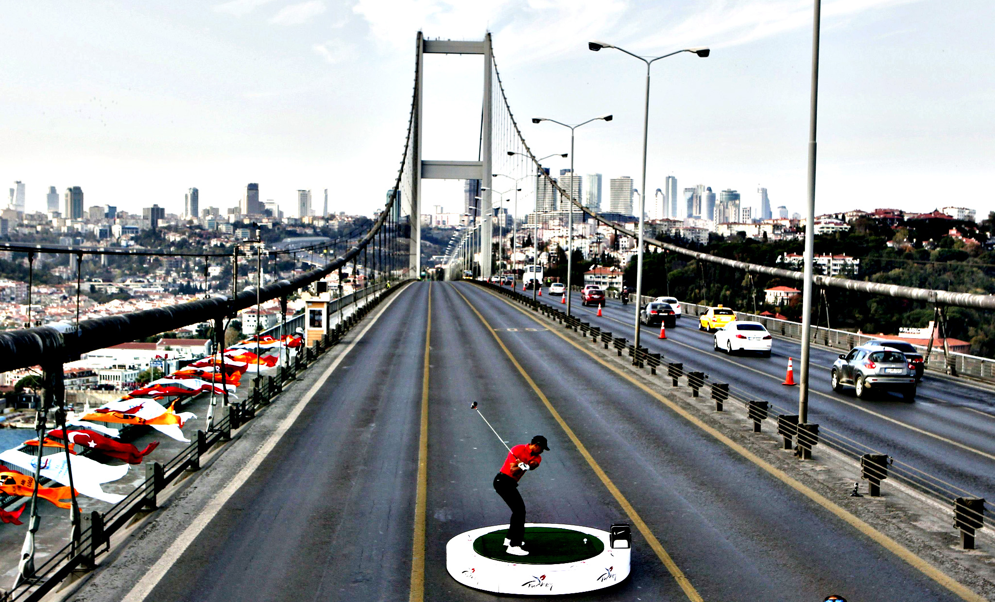 U.S. golfer Tiger Woods hits a shot during an event to promote the upcoming Turkish Airlines Open golf tournament, on the Bosphorus Bridge that links the city's European and Asian sides, in Istanbul November 5, 2013. Woods is in Turkey to attend the tournament, which will take place in Antalya, southern Turkey, between November 7 to 10.