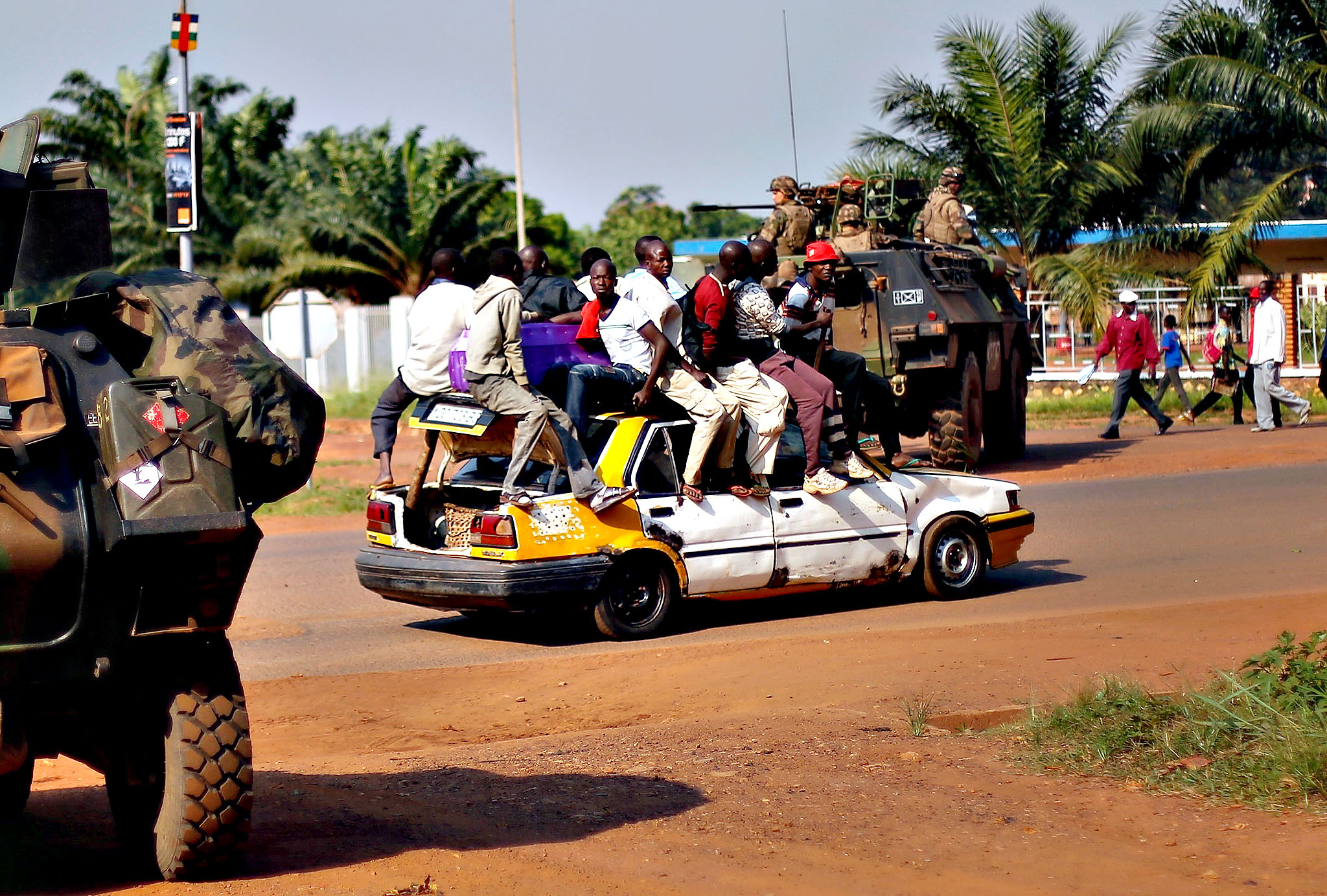 A packed taxi drives past a French checkpoint in Bangui, Central African Republic, Monday Dec. 16, 2013. Over 1600 French troops have been deployed to the country in an effort to put an end to sectarian violence.  More than 600 people have been killed since Anti-Balaka launched a strike over Bangui last week before being pushed back.