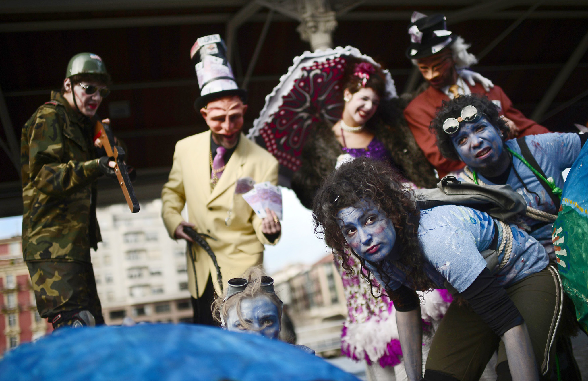 Actors take part in street theatre organized by the Coordinator of NGO's of the Basque Country in Bilbao...Actors take part in street theatre organized by the Coordinator of NGO's of the Basque Country in Bilbao December 19, 2013. The organization, an umbrella group for 84 Basque NGO's, performed Quien es Quien (Who's Who), an improvised theatrical piece, dressed as bankers, the wealthy and military personnel, handing out fake money to motorists and passers-by. The action was designed to draw attention to what the coordinator claims are the causes of poverty and inequality in the world. REUTERS/Vincent West (SPAIN - Tags: POLITICS CIVIL UNREST)