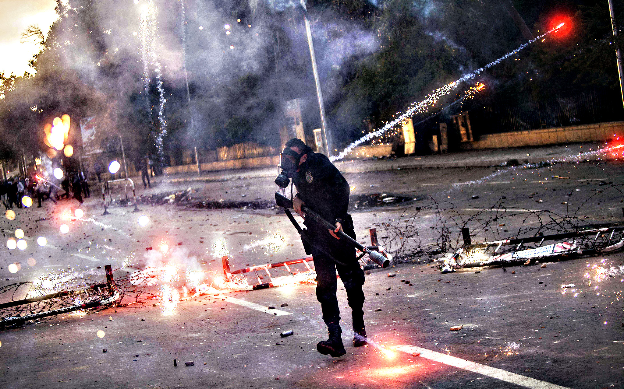 Egyptian students who support the Muslim Brotherhood (background) shoot fireworks at riot policemen (foreground) during clashes outside the University of Cairo campus in the capital