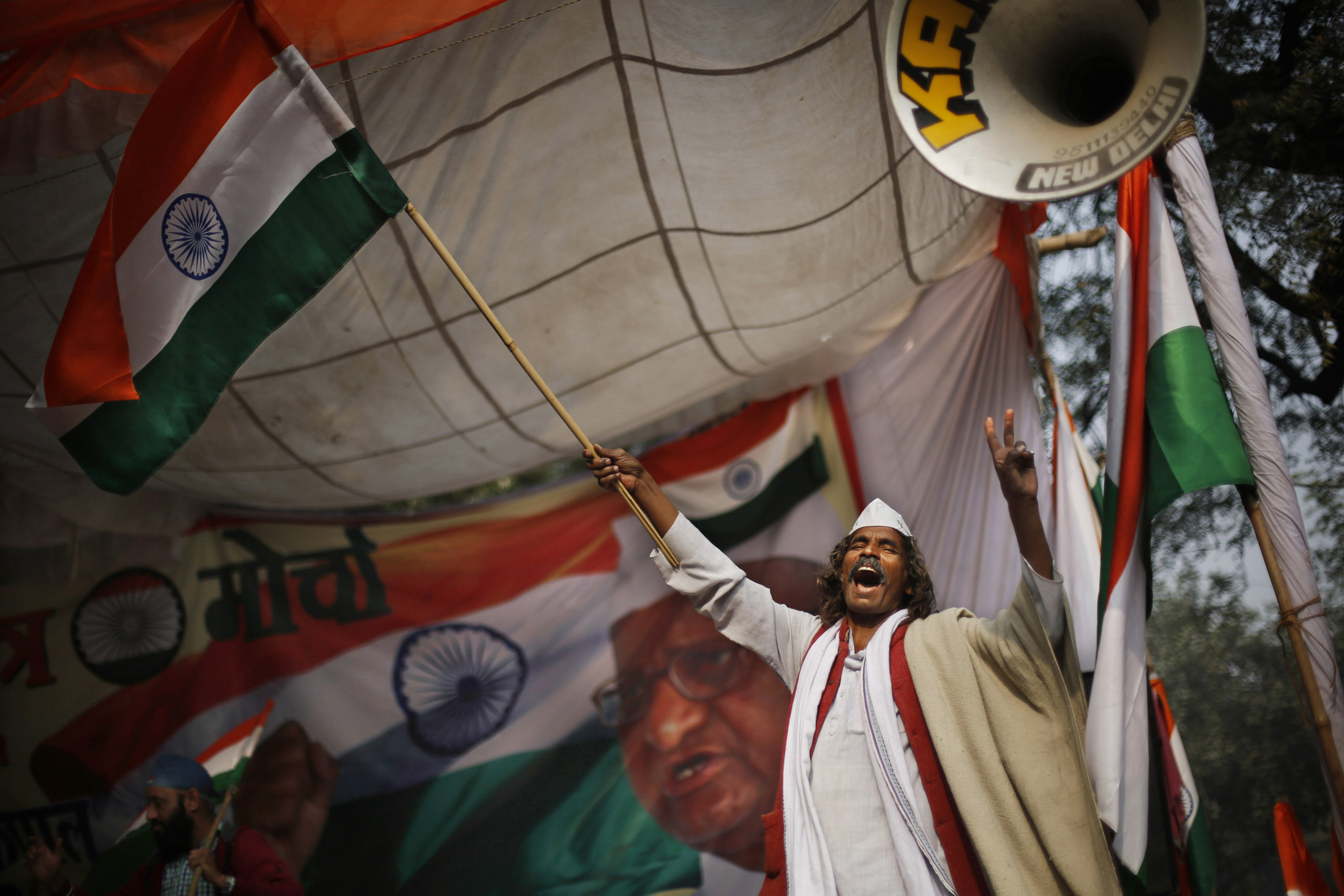 "A supporter of social movement leader Anna Hazare waves the national flag as he celebrates the news of passing of a contentious anti-graft bill that empowers an independent ombudsman to investigate and prosecute cases of corruption by politicians and bureaucrats, in New Delhi, India, Wednesday, Dec. 18, 2013. The ""Lokpal,"" or watchdog, bill was passed by the lower house of Parliament on Wednesday after the government agreed to several amendments suggested by opposition lawmakers. Hazare has been on a hunger strike for the last nine days to insist that both houses of Parliament adopt the bill. (AP Photo/Altaf Qadri)"