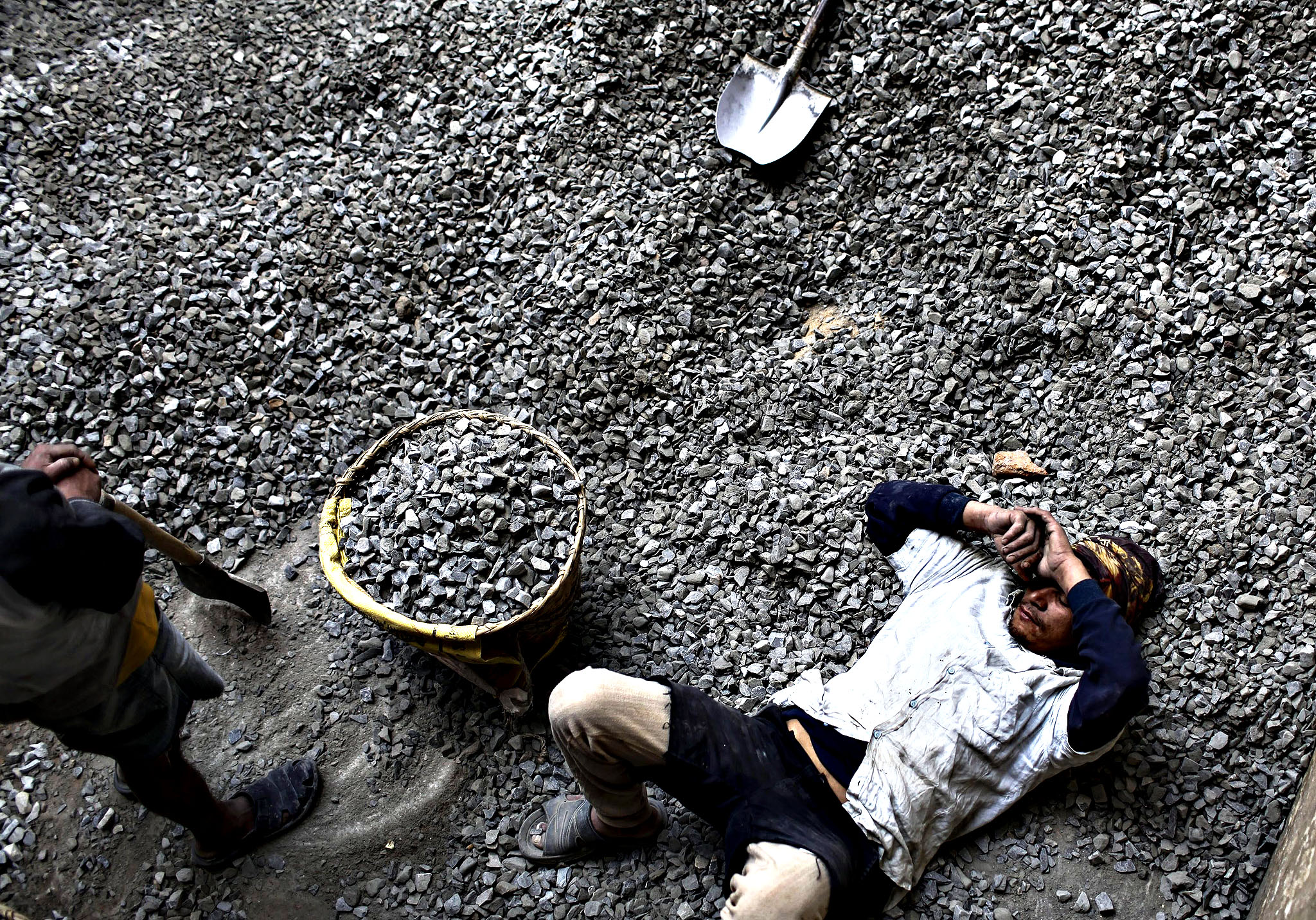 A Nepalese domestic worker rests at a construction site in Kathmandu, Nepal, 16 December 2013. According to reports, more than 300,000 Nepalese youth leaving the country each year due to lack of proper job opportunities in the country.