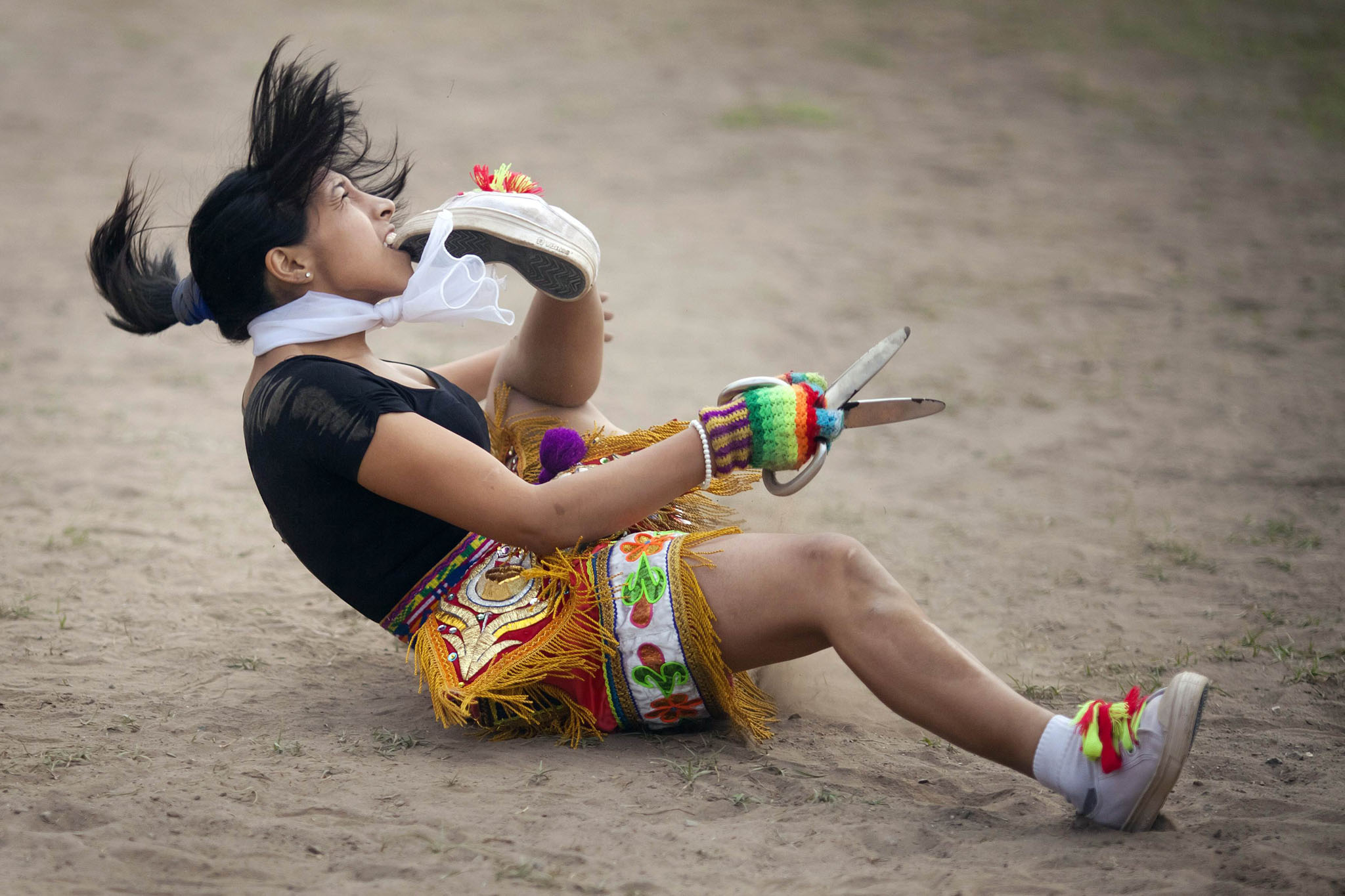 "A ""scissors"" dancer grabs her shoe with her mouth while performing in a national scissors dance competition in the outskirts of Lima"