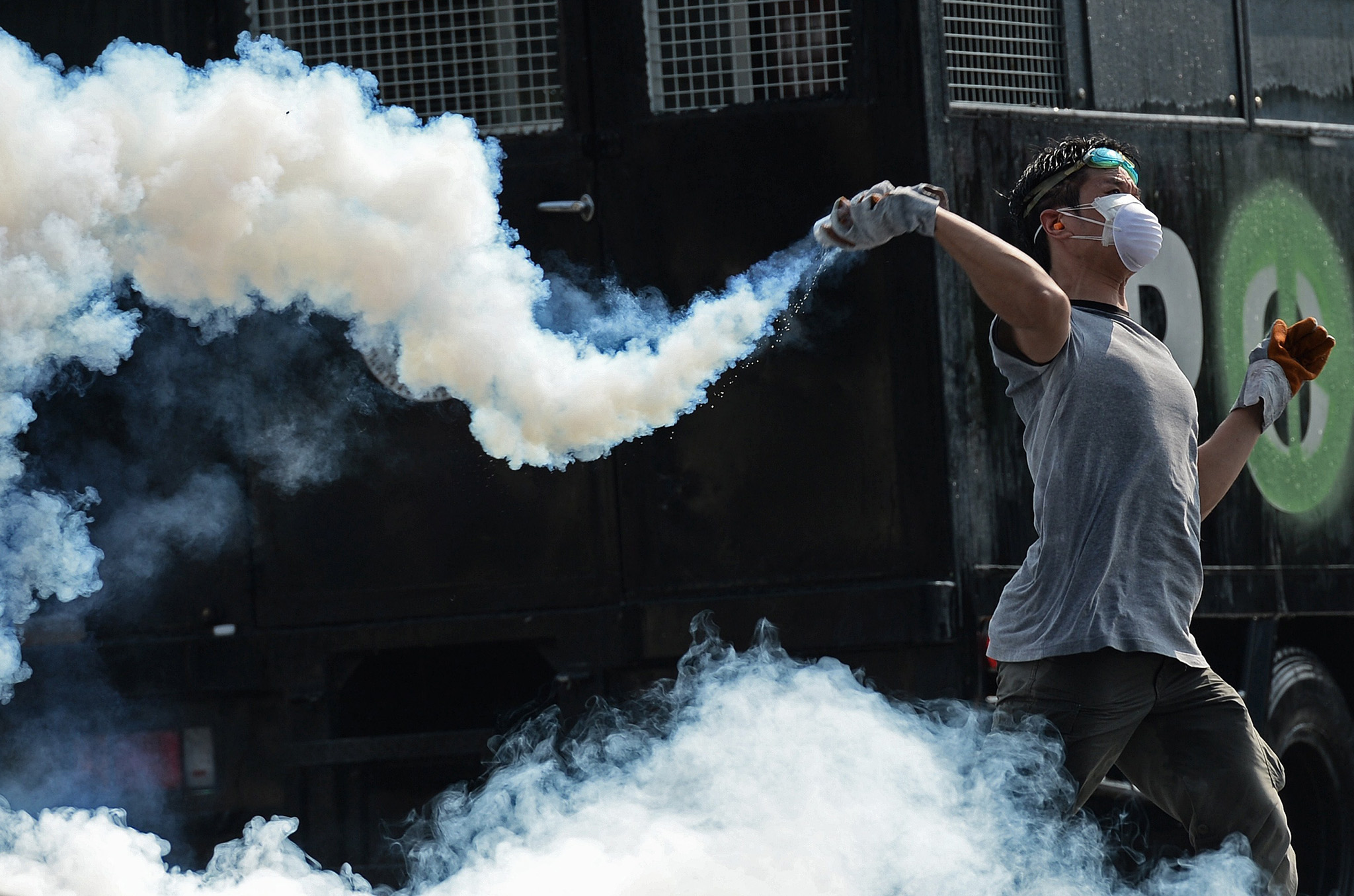 A Thai anti-government protester throws a tear gas canister back to the police during an ongoing rally outside Government House in Bangkok.
