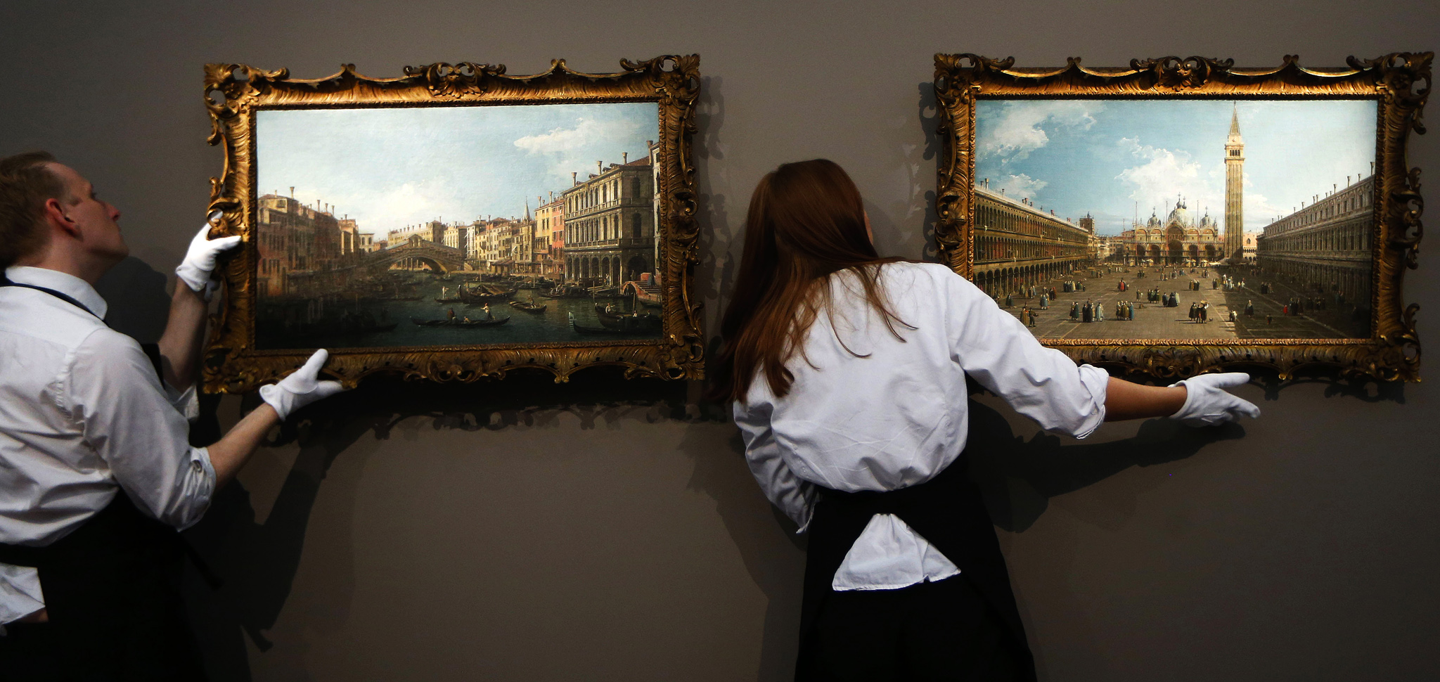 Sotheby's employees hang up the paintings 'A View of the Grand Canal and Rialto Bridge', left, and 'A View of the Piazza San Marco looking East towards the Basilica' by Canaletto on display at the auction house in London. The paintings are to be auctioned as a pair in 'Old Master and British Paintings' sale on Dec. 4 with an estimated price of 8 to 12 million pounds (US$12.44 to 18.66 million or 9.3 to 13.94 million euro).