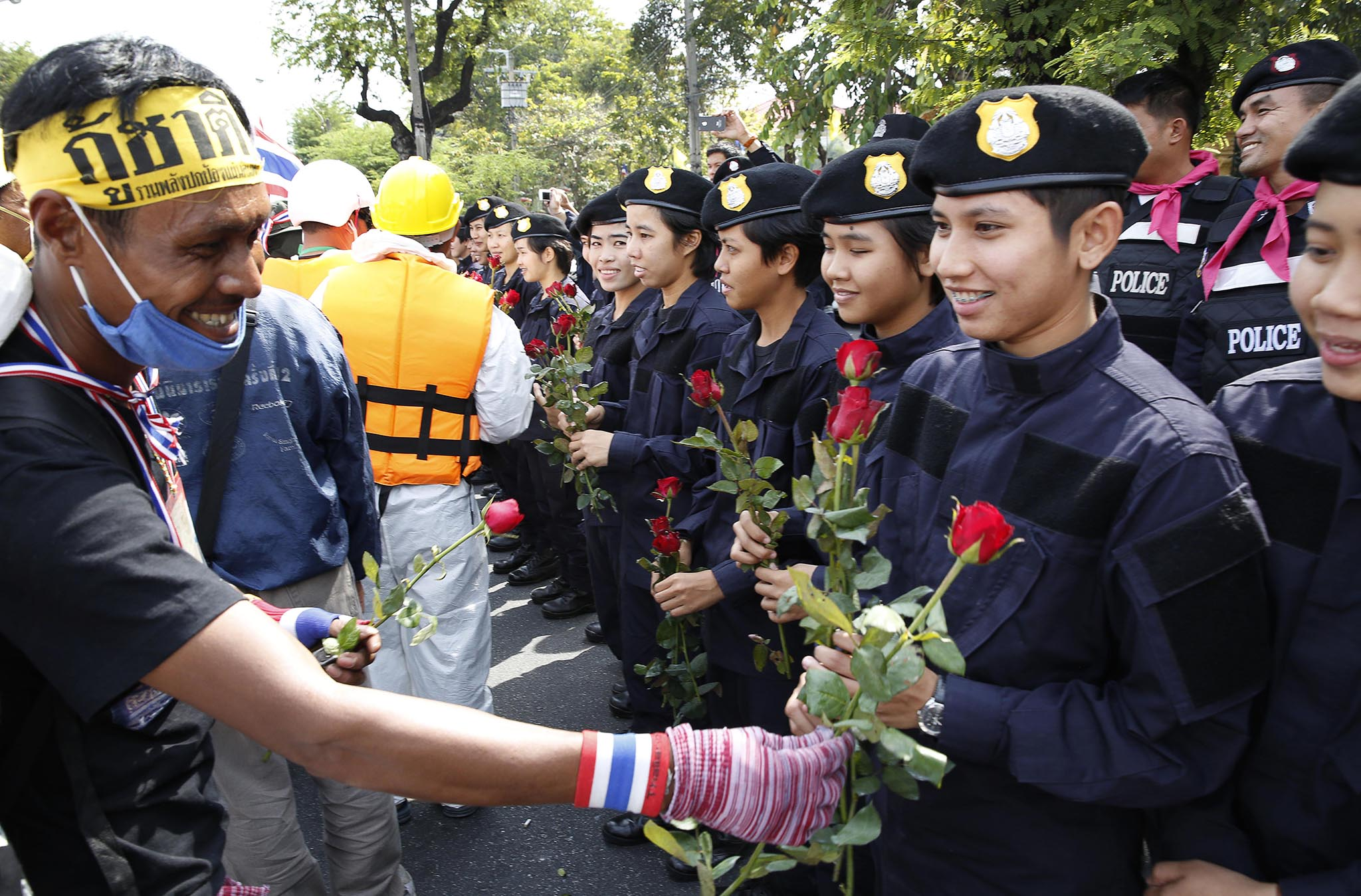 An anti-government protester gives roses to Thai policewomen outside city police headquarters in Bangkok, Thailand Tuesday, Dec. 3, 2013. Anti-government protesters swarmed into the Thai prime minister's office compound Tuesday as police stood by and watched, allowing them to claim a symbolic victory after three days of bitter clashes. Hundreds of protesters poured onto the lawn of Government House, waving Thai flags and blowing whistles to celebrate a symbolic victory. (AP Photo /Manish Swarup)