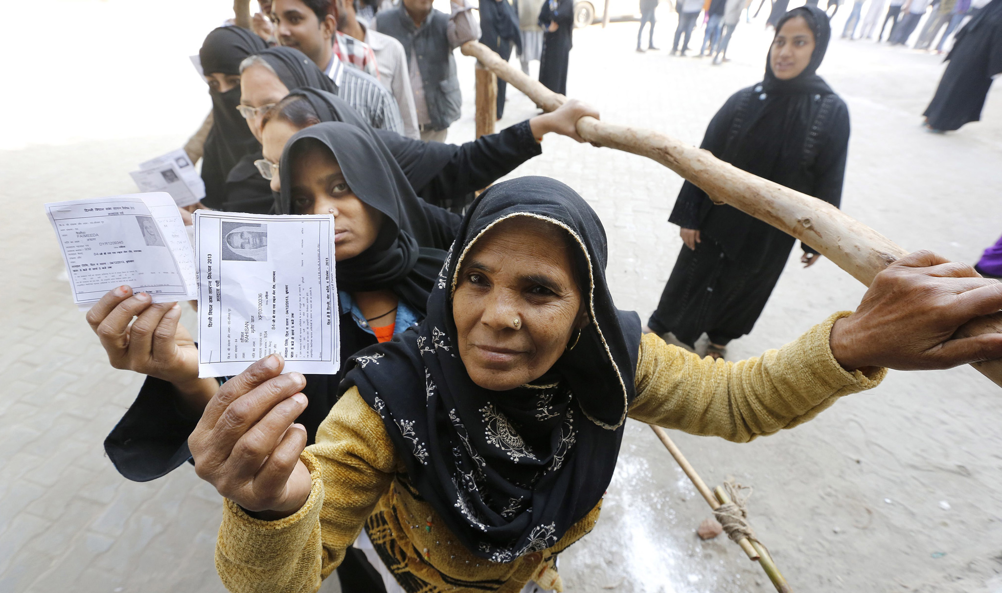 Voters line up to show their voter ID cards at a polling station in Seelampur, east Delhi, India. State assembly elections were held in the Indian capital, regarded as a test for general elections scheduled for 2014.