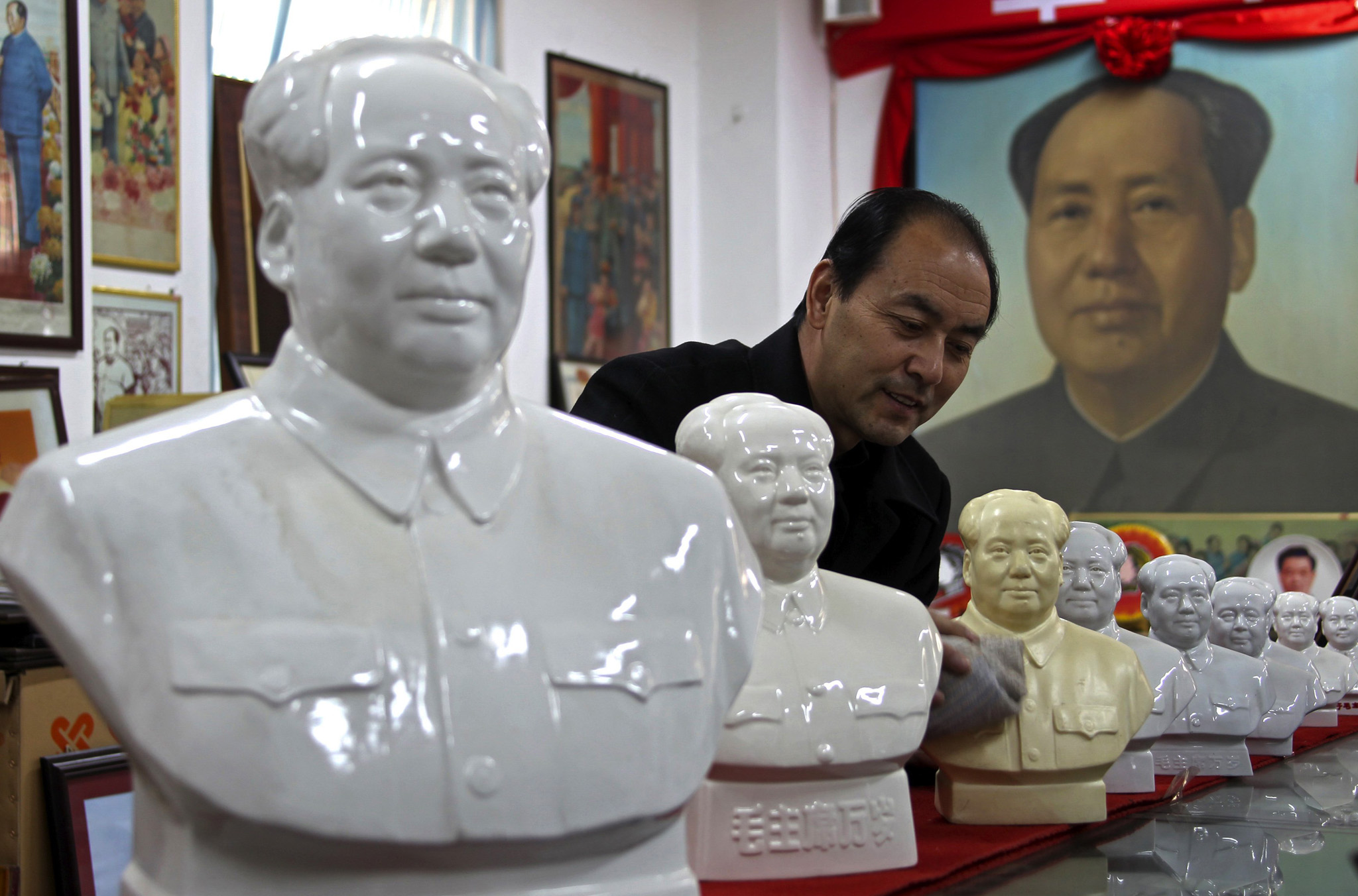 Dang Guihong, a judicial official, wipes statues of China's late Chairman Mao Zedong at an exhibition room in Yuncheng, Shanxi province. Dang is going to exhibit around 5000 pieces of his revolution collection, including badges, statues and portraits ahead of the 120th anniversary of Mao's birth.