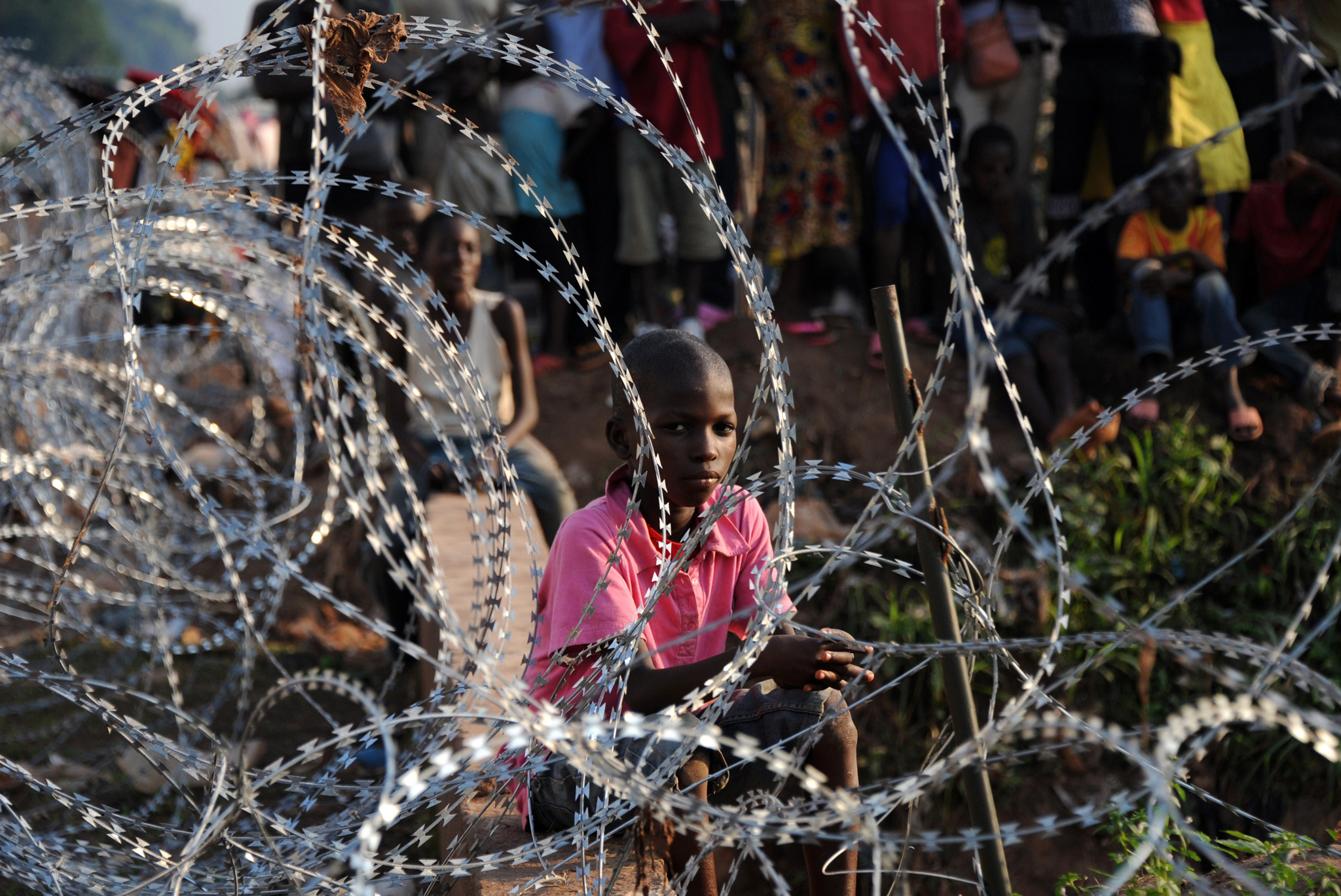 A child sits next to barbed wire as people stand in a refugee camp near the airport in Bangui, Central African Republic, after fleeing violence.