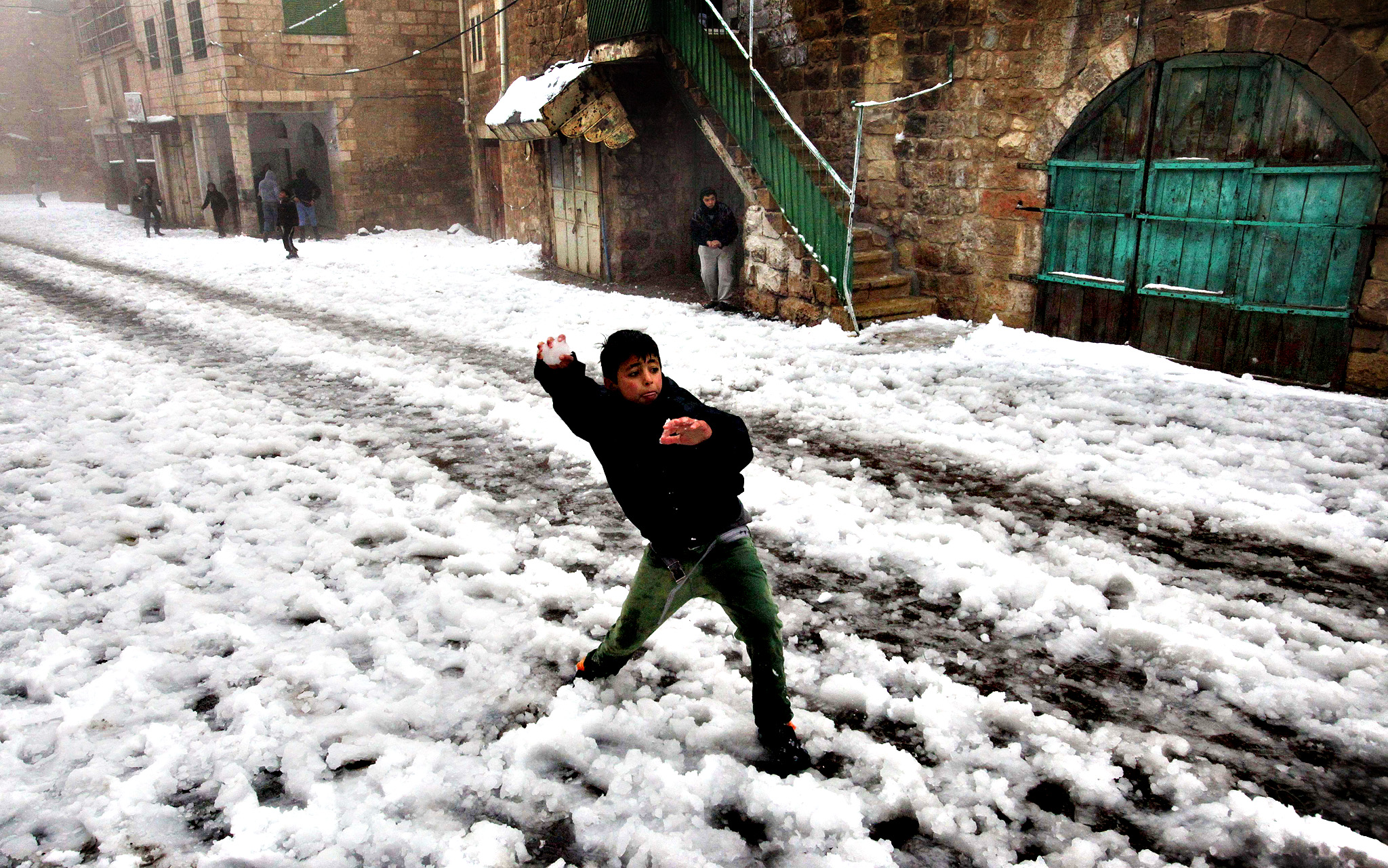 A Palestinian boys throws a snowball near Ibrahimi Mosque or the Tomb of the Patriarch, a religious site to both Muslims and Jew, in the West Bank town of Hebron as snow falls on December 12, 2013. A bruising winter storm brought severe weather to the Middle East, forcing the closure of roads and schools and blanketing much of the high altitude areas with snow and ice.