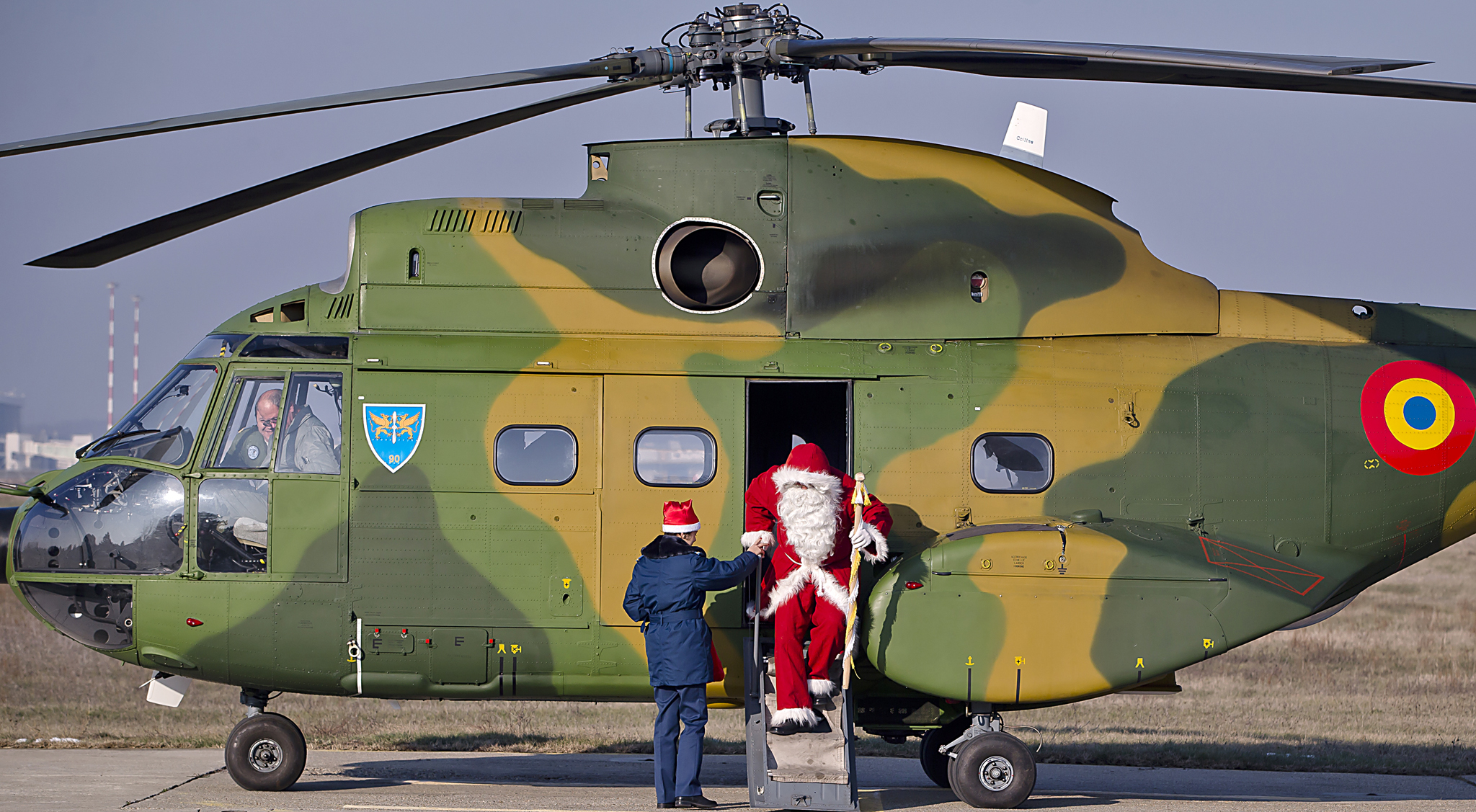 A man wearing a Santa Claus outfit receives help to exit a helicopter at the Romanian Airforce Base 90 in Otopeni, outside Bucharest, Romania, Tuesday, Dec. 17, 2013. Santa arrived on a Puma helicopter and distributed gifts to the children of the Romanian air force personnel .