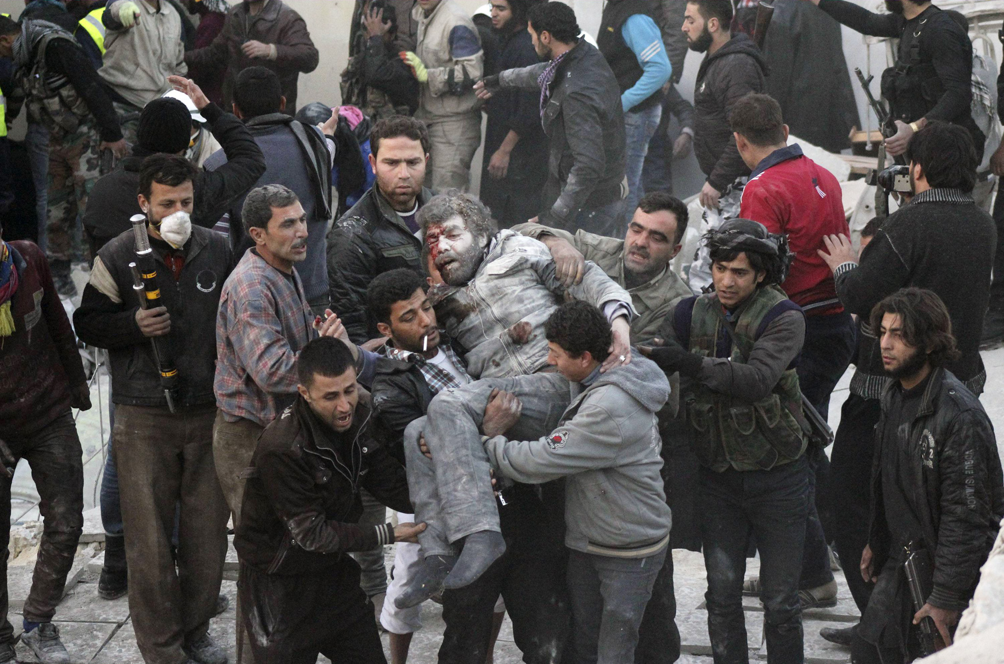 SYR29  Residents carry an injured man that survived shelling after what activists said was an air strike from forces loyal to Syria's President Bashar al-Assad in Takeek Al-Bab area of Aleppo.