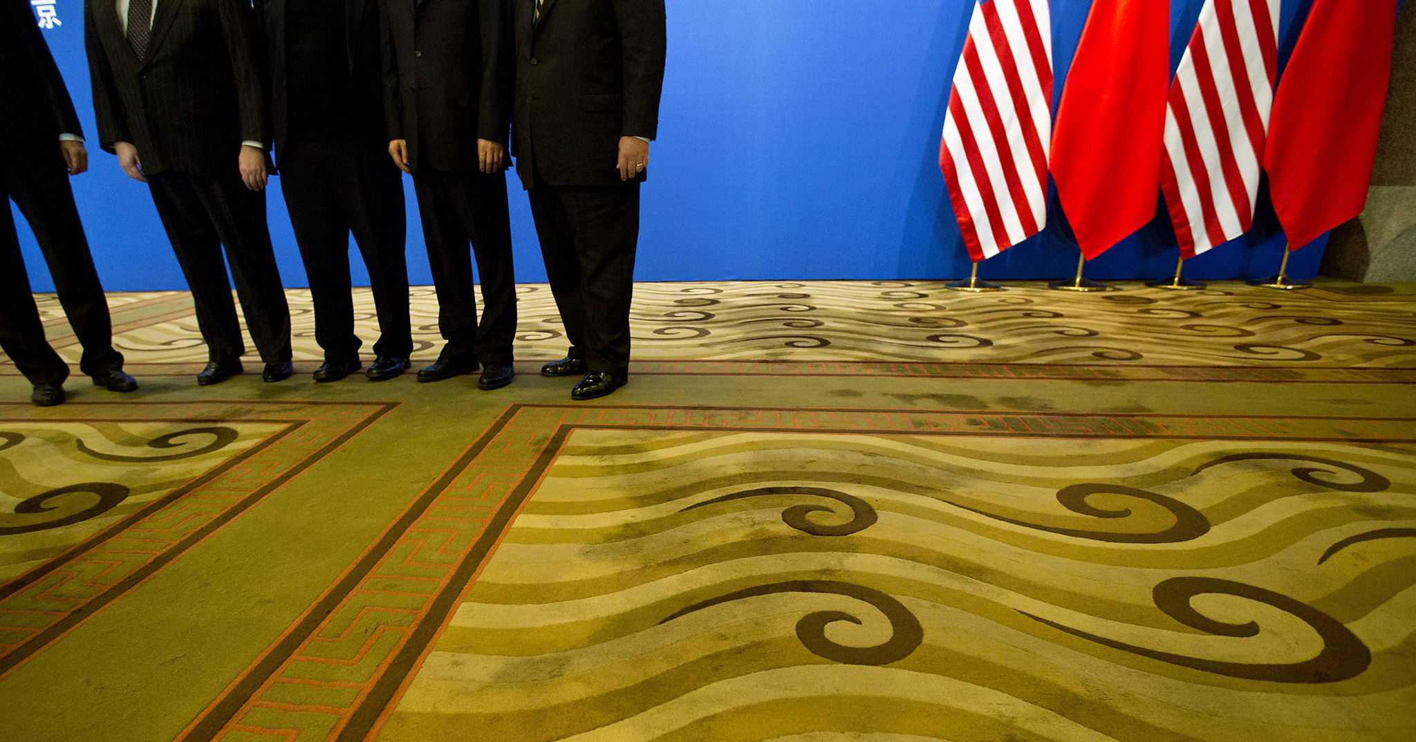 Officials pose for photos near U.S. and Chinese national flags in a meeting room before the opening session of the 24th China-U.S. Joint Commission on Commerce and Trade at Diaoyutai State Guesthouse in Beijing, Friday, Dec. 20, 2013.