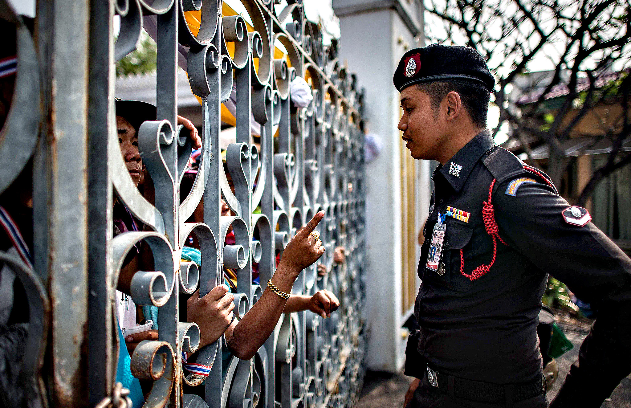 An anti-government demonstrator points his finger at a policeman as they talk through the gate of the Government House in Bangkok on December 12, 2013.  Political turmoil has been rocking the Thai capital for weeks, with protesters seeking to oust Prime Minister Yingluck Shinawatra and rid the kingdom of the influence of her brother, deposed former leader Thaksin.