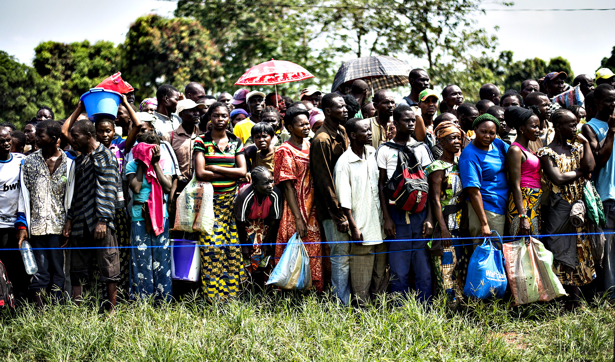 People queue to receive aid near a camp for internally displaced persons (IDP) in Bangui on December 13, 2013. Aid workers warned of a looming humanitarian crisis in the Central African capital as the UN said more than 600 people have been killed in sectarian violence in the past week and tens of thousands of residents desperate for protection have fled their homes.