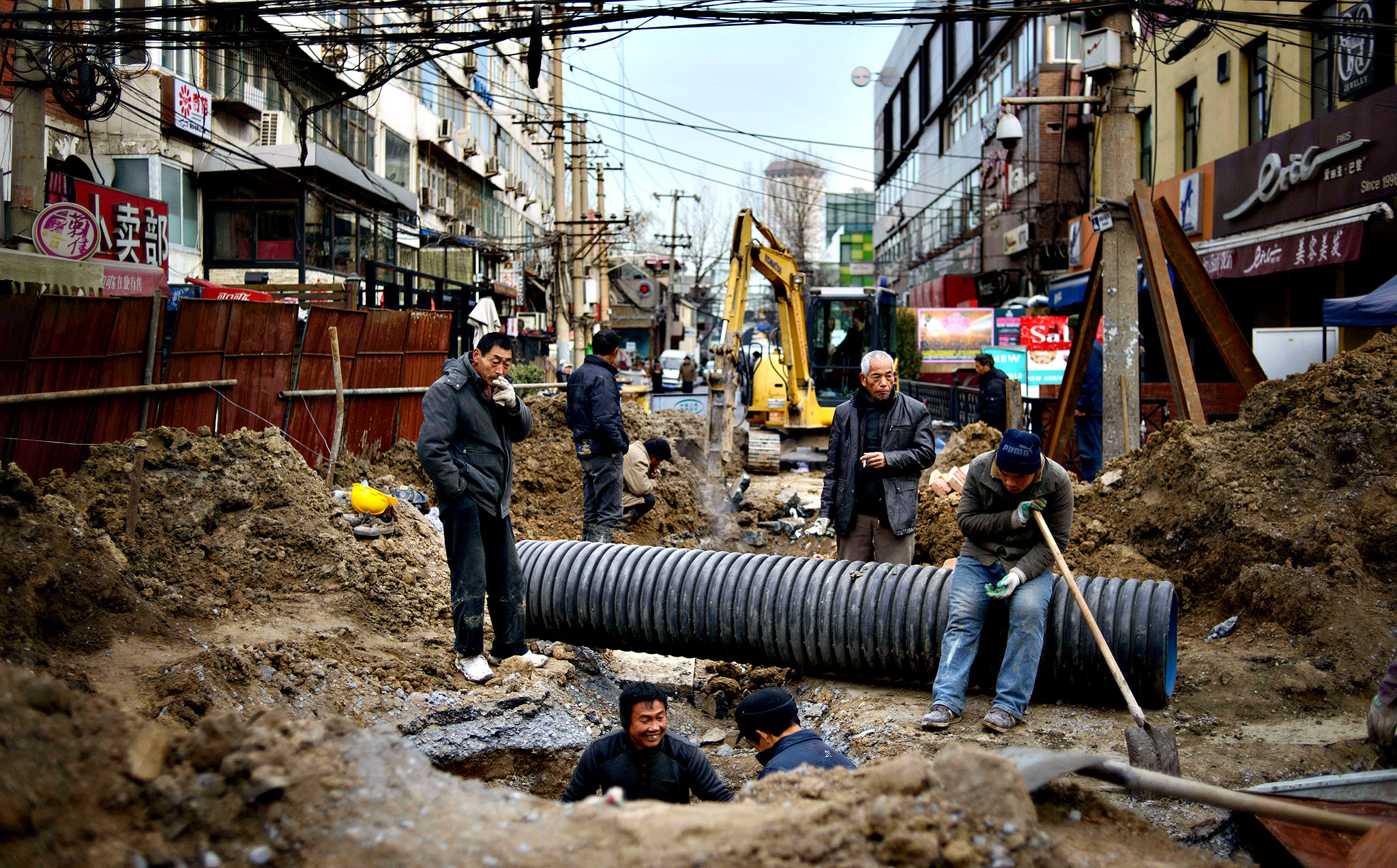 Workers undertake drainage repairs on a street on a commercial street in Beijing on December 10, 2013. Chinese inflation decelerated to 3.0 percent in November, the National Bureau of Statistics (NBS) said, well under the government's target for the year.