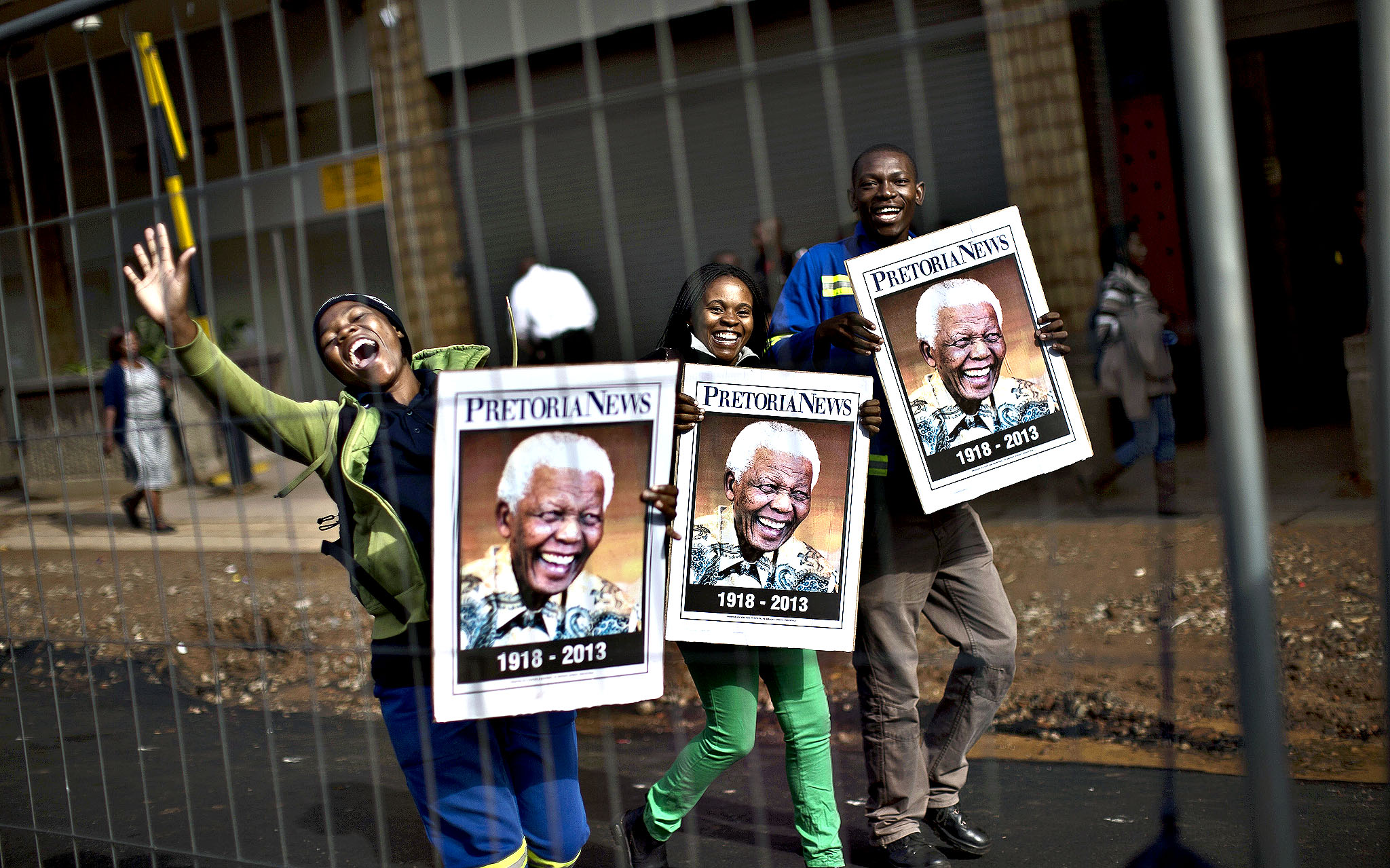 South African mourners hold posters of former president Nelson Mandela, while chanting slogans as the convoy transporting the body of Nelson Mandela passes by, in Pretoria, South Africa, Wednesday, Dec. 11, 2013. Motorcycle-riding police officers escorted the casket Wednesday morning from 1 Military Hospital outside of Pretoria to the Union Buildings. Some Pretoria residents lined the streets to watch the procession go by, singing tributes to Mandela, who died Dec. 5 at age 95.