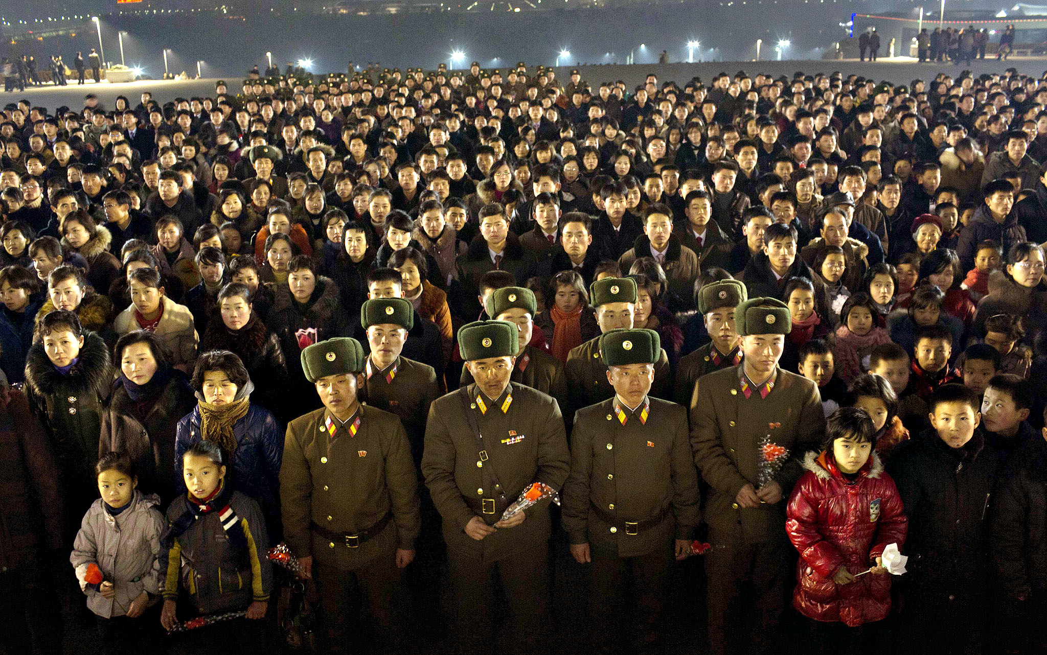 North Koreans gather together on the steps of Mansu Hill to lay flowers at the base of statues of the late leaders, Kim Il Sung and Kim Jong Il, in Pyongyang, North Korea, Monday, Dec. 16, 2013, the eve of the second anniversary of the death of Kim Jong Il.
