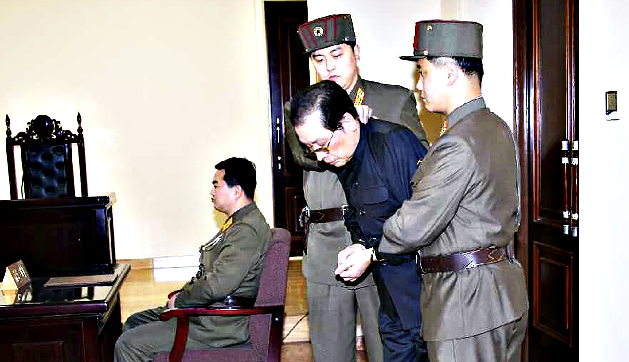 Jang Song Thaek, with his hands tied with a rope, is dragged into the court by uniformed personnel in this December 13, 2013 picture taken from Rodong Sinmun December 12, 2013 and released by Yonhap. North Korea said on Friday that Jang, the uncle of leader Kim Jong Un, previously considered the second most powerful man in the secretive state, has been executed for treason, the biggest upheaval since the death of Kim's father two years ago.