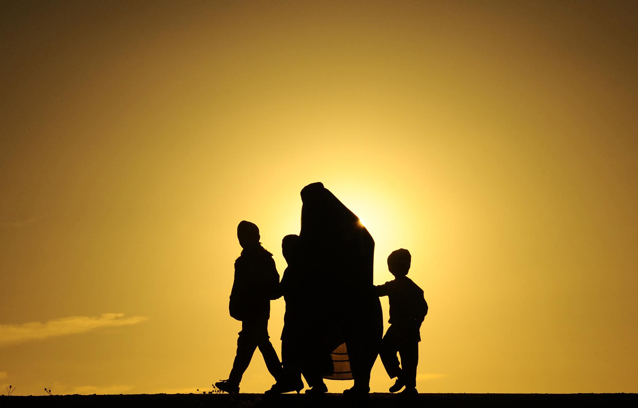 An Afghan family walks during sunset in