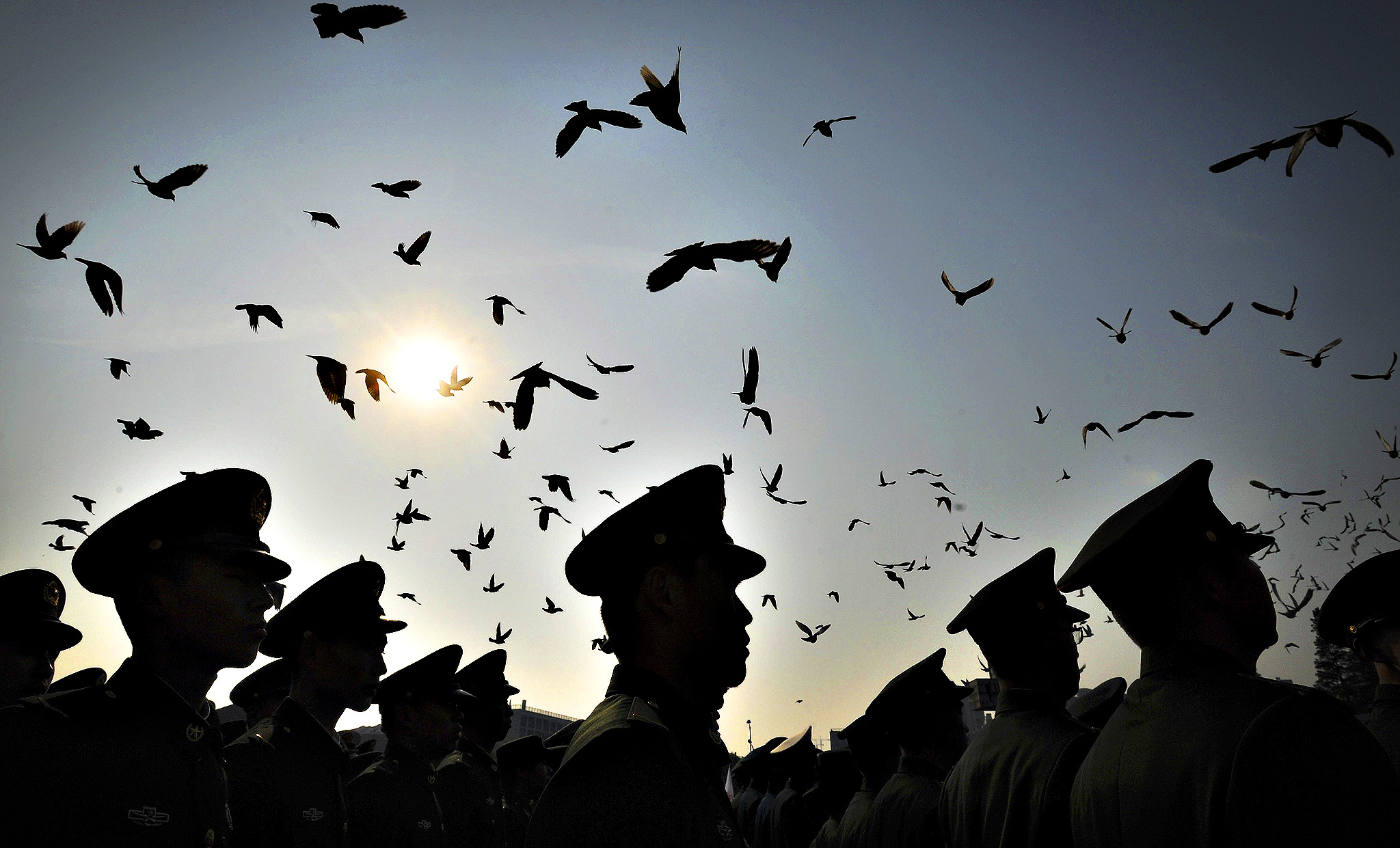 Doves fly above Chinese paramilitary policemen as they gather to mourn for the victims of 1937 Nanjing Massacre at the Nanjing Massacre Memorial Hall in Nanjing in east China's Jiangsu province Friday, Dec. 13, 2013. Nanjing on Friday marked 76 years after a bloody invasion by the Japanese imperial army that remains as one of the most sensitive friction points in the shared history of two Asian powers.