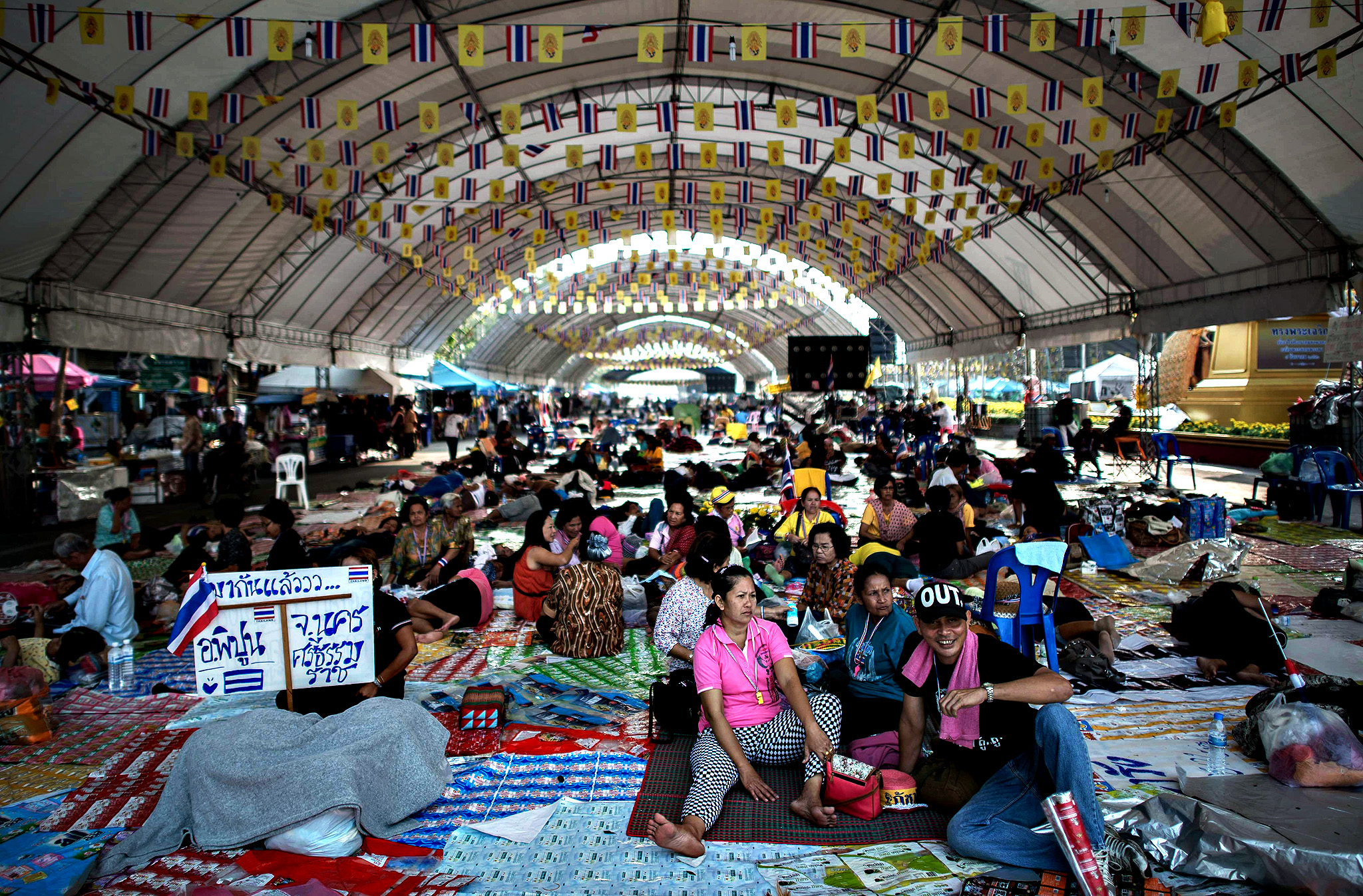 Anti-government demonstrators sit in the shade at a protest site near the democracy monument in Bangkok on December 13, 2013.  Political turmoil has been rocking the Thai capital for weeks, with protesters seeking to oust Prime Minister Yingluck Shinawatra and rid the kingdom of the influence of her brother, deposed former leader Thaksin.