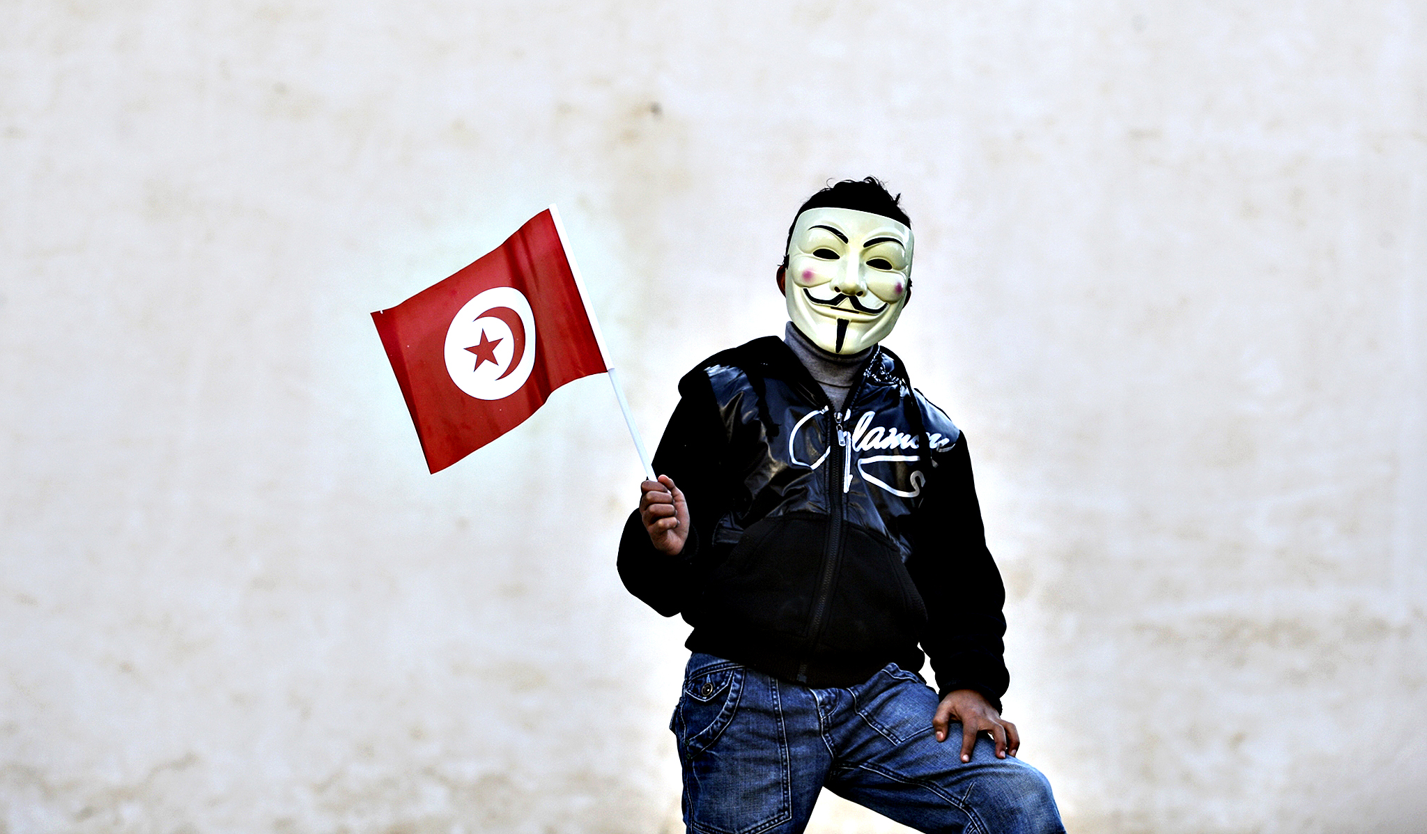 A civilian wearing a mask holds a Tunisian flag in Sidi Bouzid, central Tunisia, Tuesday, Dec. 17, 2013 to mark the third anniversary of the Tunisian uprising. Several political groups gather at the square where Mohamed Bouazizi's self-immolation on Dec. 17, 2010 triggered mass protests against social marginalisation and government corruption in Tunisia.
