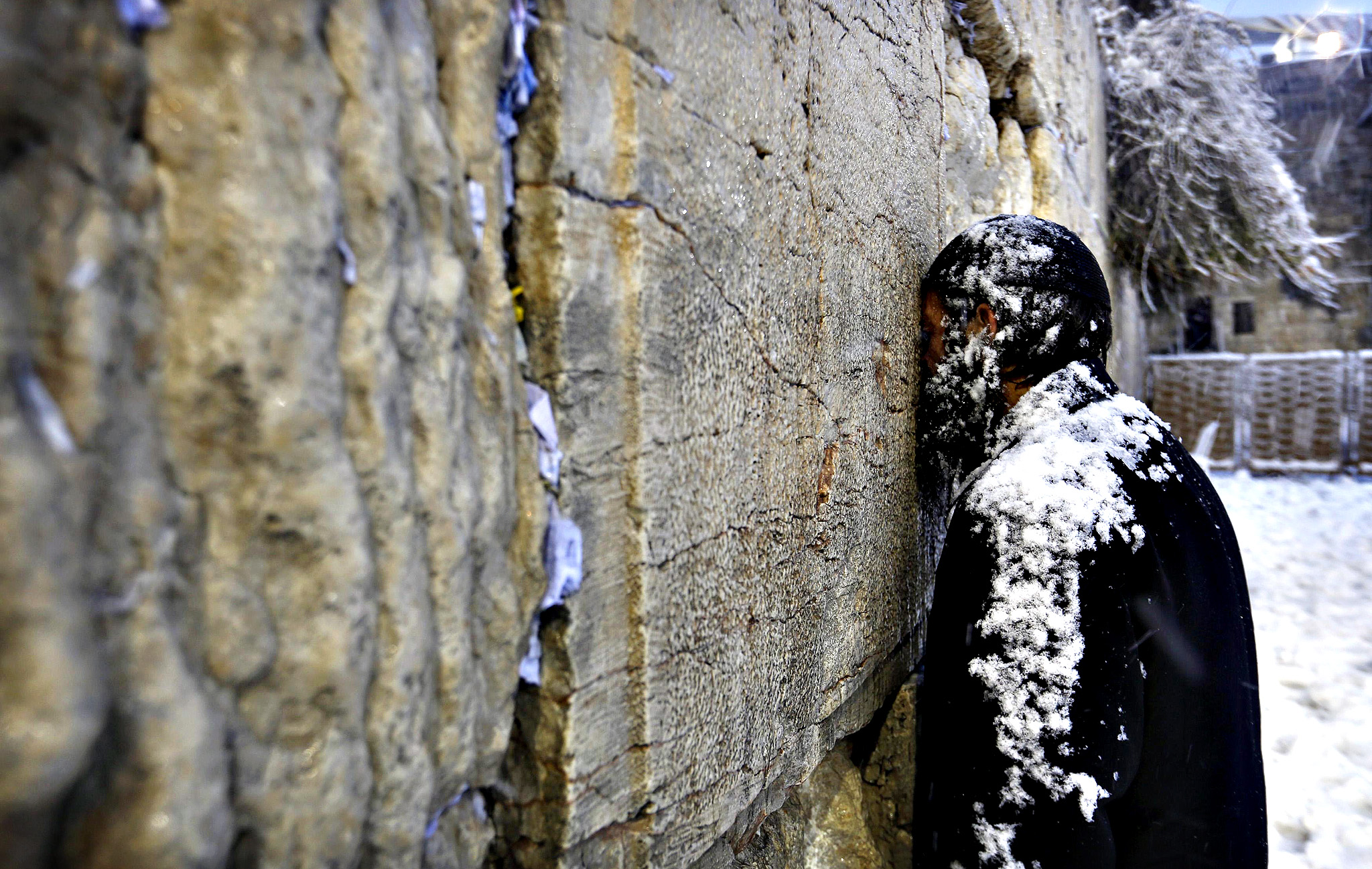 An Ultra-Orthodox Jewish man prays at  the Western Wall in Jerusalem's Old City during a snowstorm.
